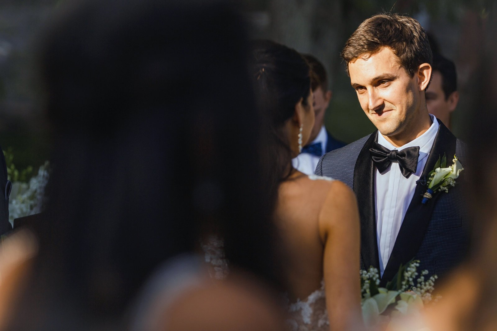 groom looking into grooms eyes during wedding ceremony at the newhall mansion