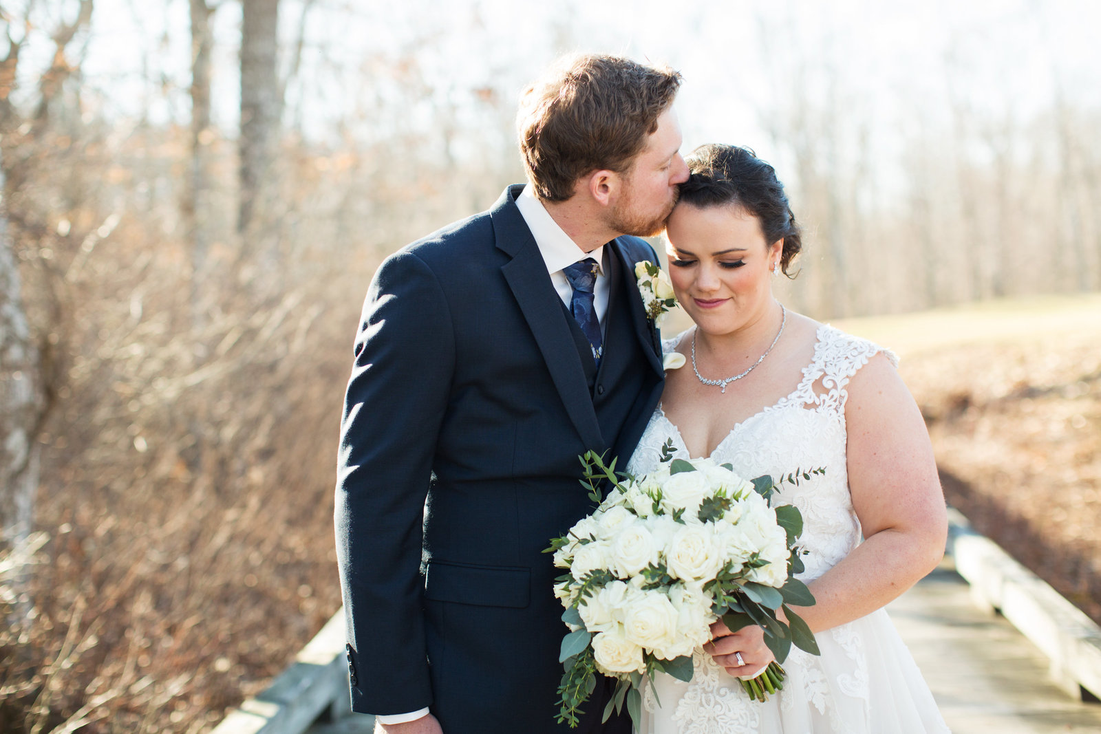 groom kisses brides head during outdoor portraits in March