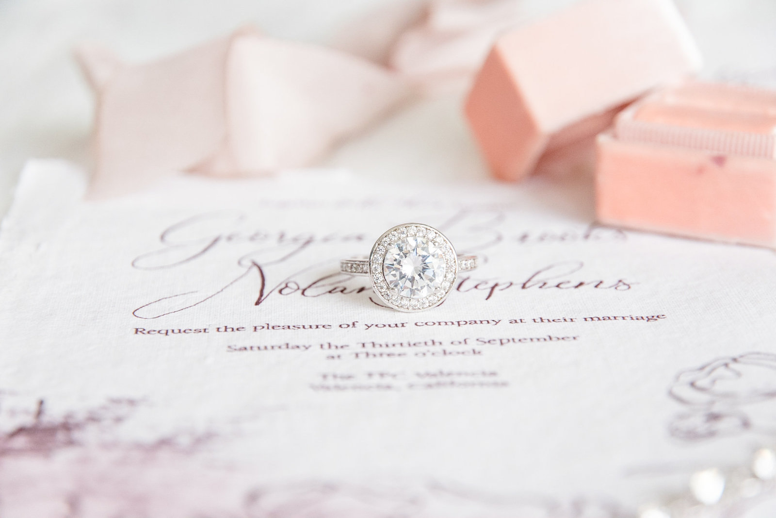 Engagement Ring lays on Invitation suite.