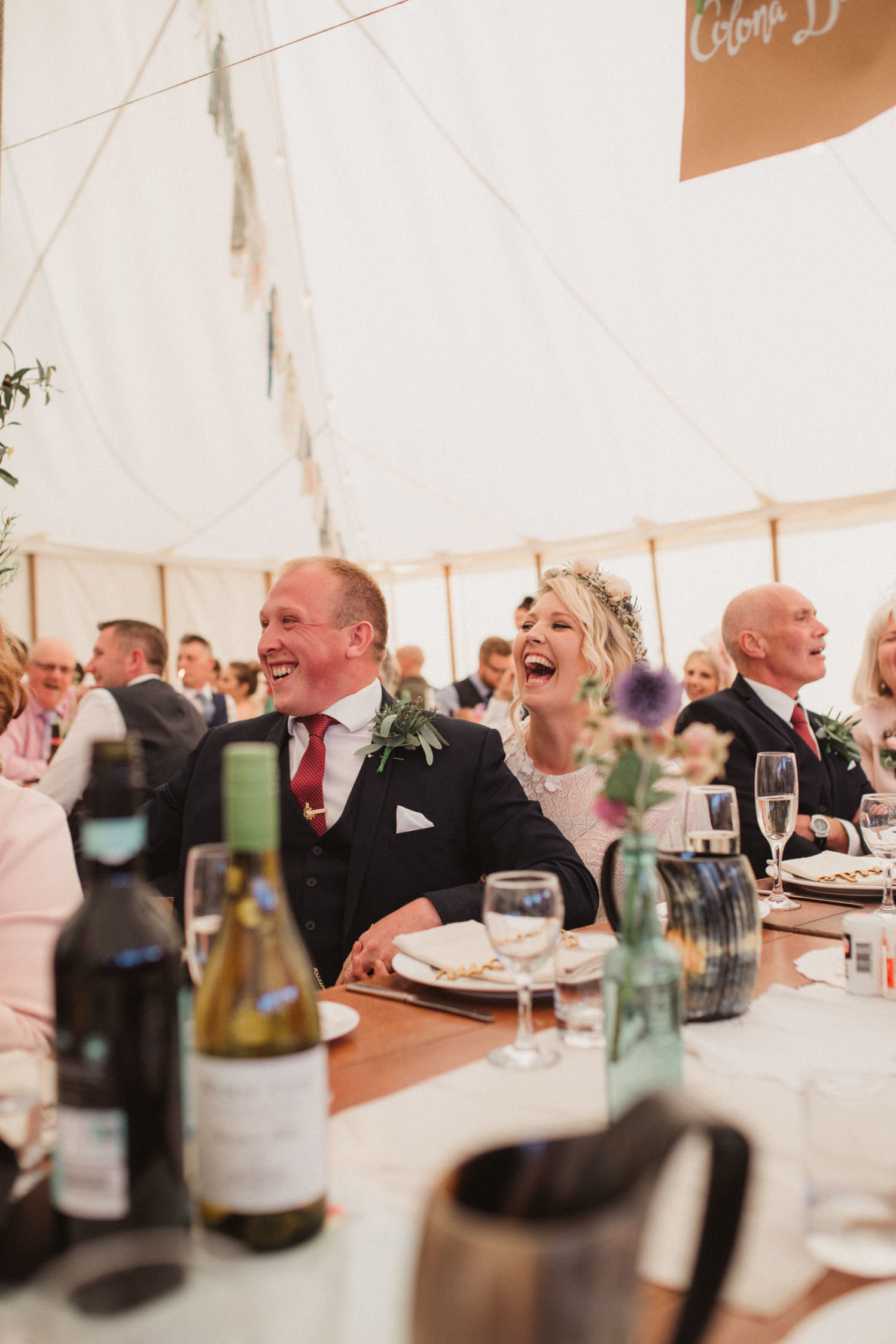 Laughing bride and groom sat in a boho marquee at their wedding in Woodbridge, Suffolk