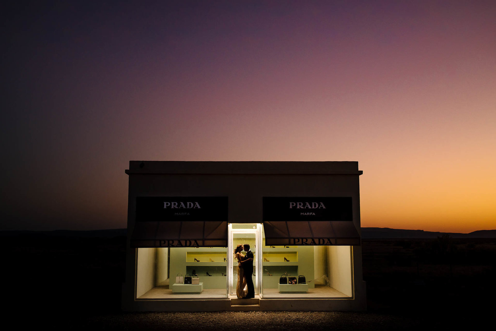 couple kissing during their marfa engagement session by the prada store in marfa