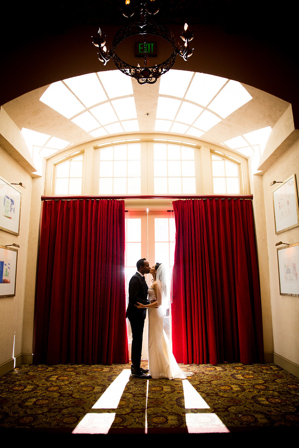 romantic kissing shot with red curtains
