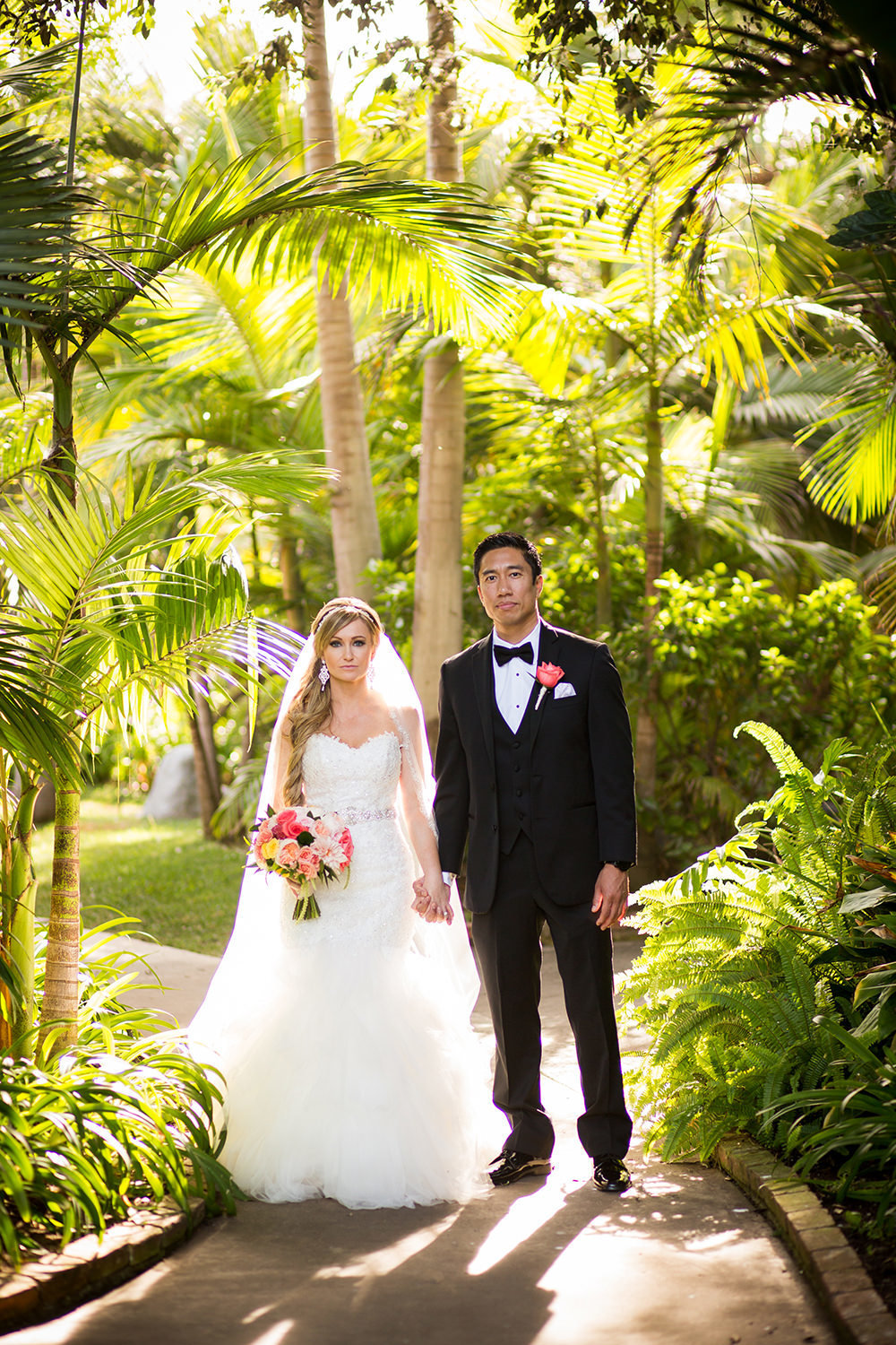 bride and groom serious with topical plants