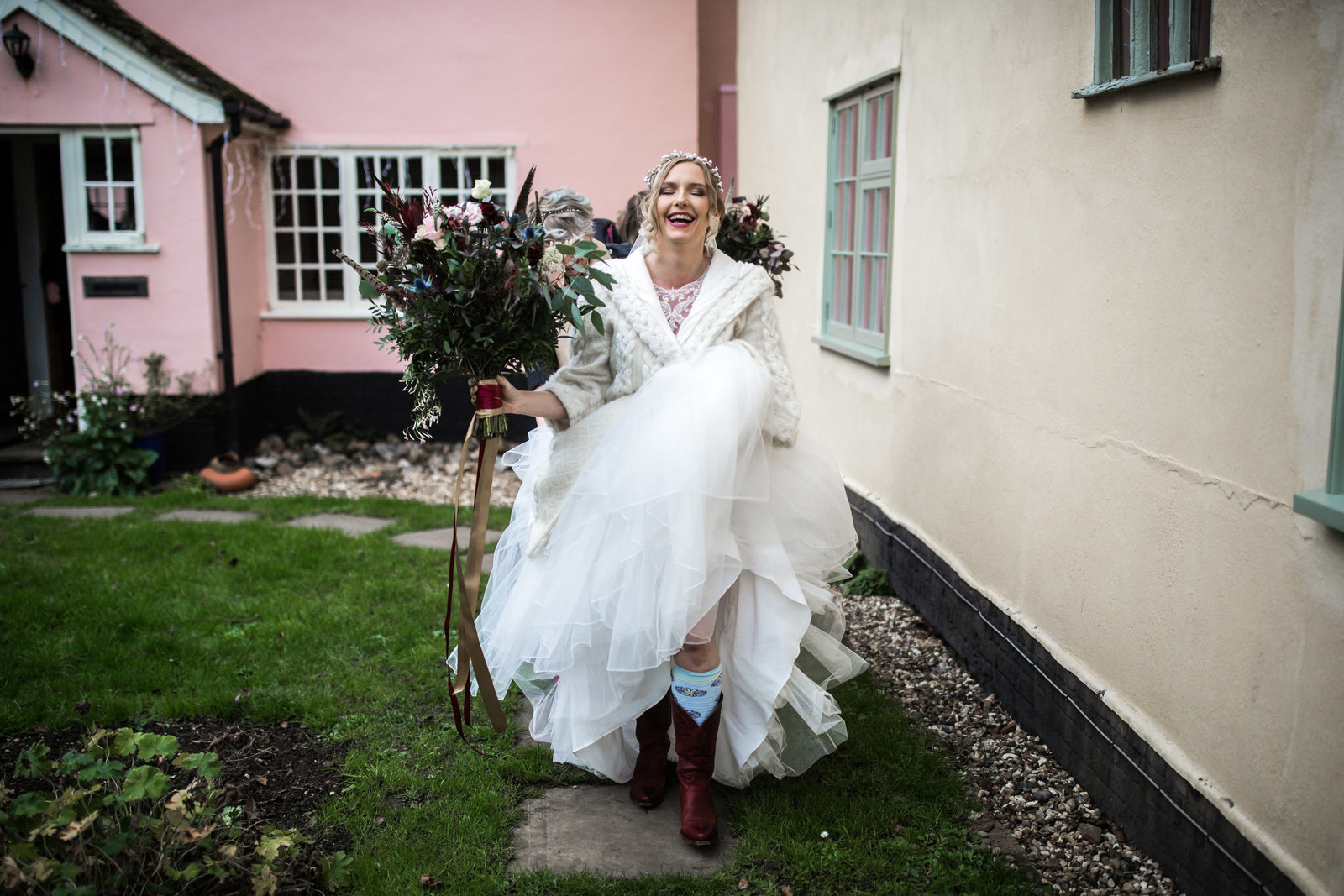 A bride walks down a path of her Norfolk home on the way to her wedding ceremony. She is wearing cowboy boots and laughing.