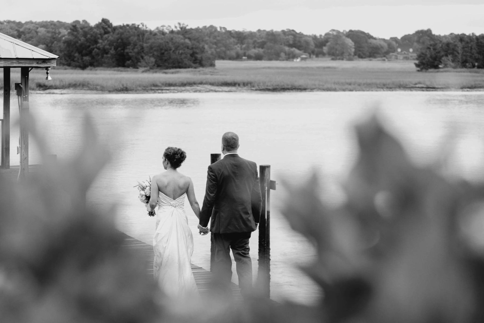 Bride and groom stand on dock, Old Wide Awake Plantation, Charleston, South Carolina