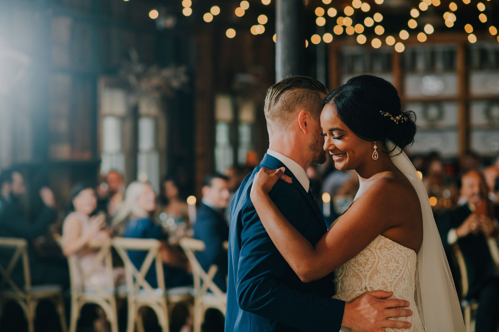 bride wearing white dress and veil clutches her grooms shoulder and leans in while they share a first dance with sparkling fairy lights in the background inside at terrain gardens by philadelphia wedding photographer alex medvick