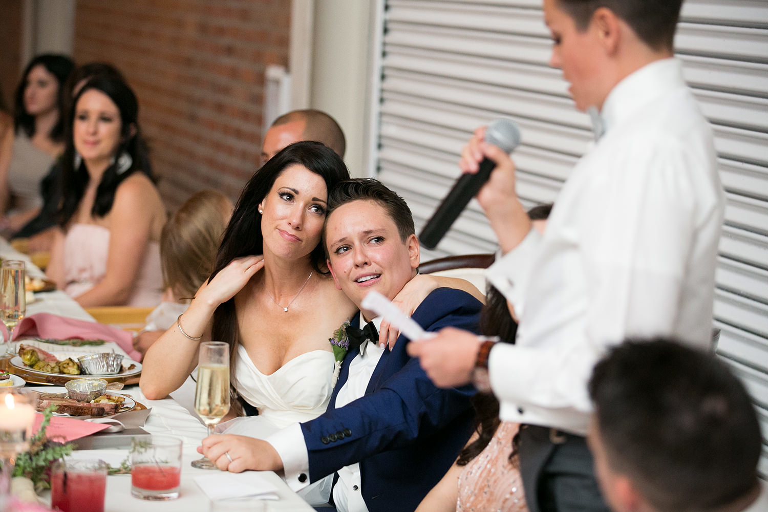 couple laughing at reception speeches brick