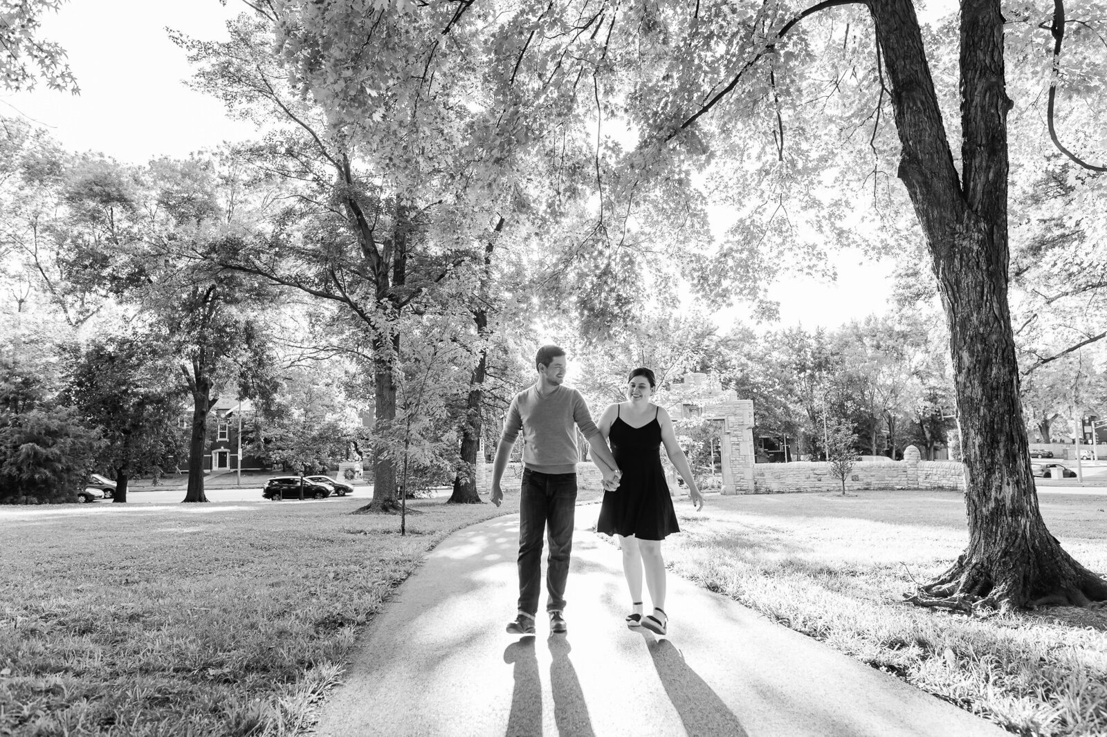 Candid engagement photo of a couple walking together in Tower Grove Park in St. Louis