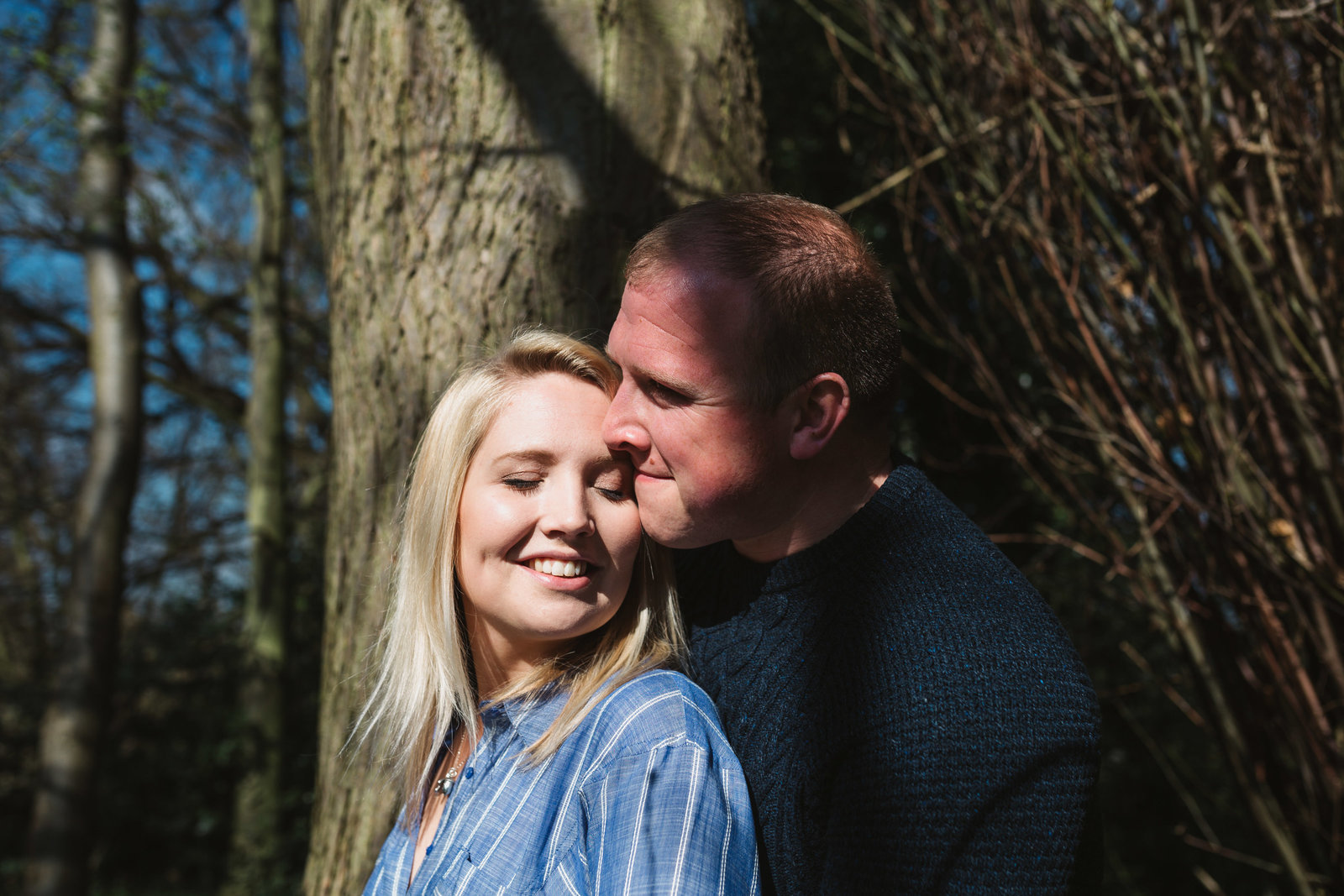 Laughing engaged couple lean against a tree in Ipswich for a natural couples photo