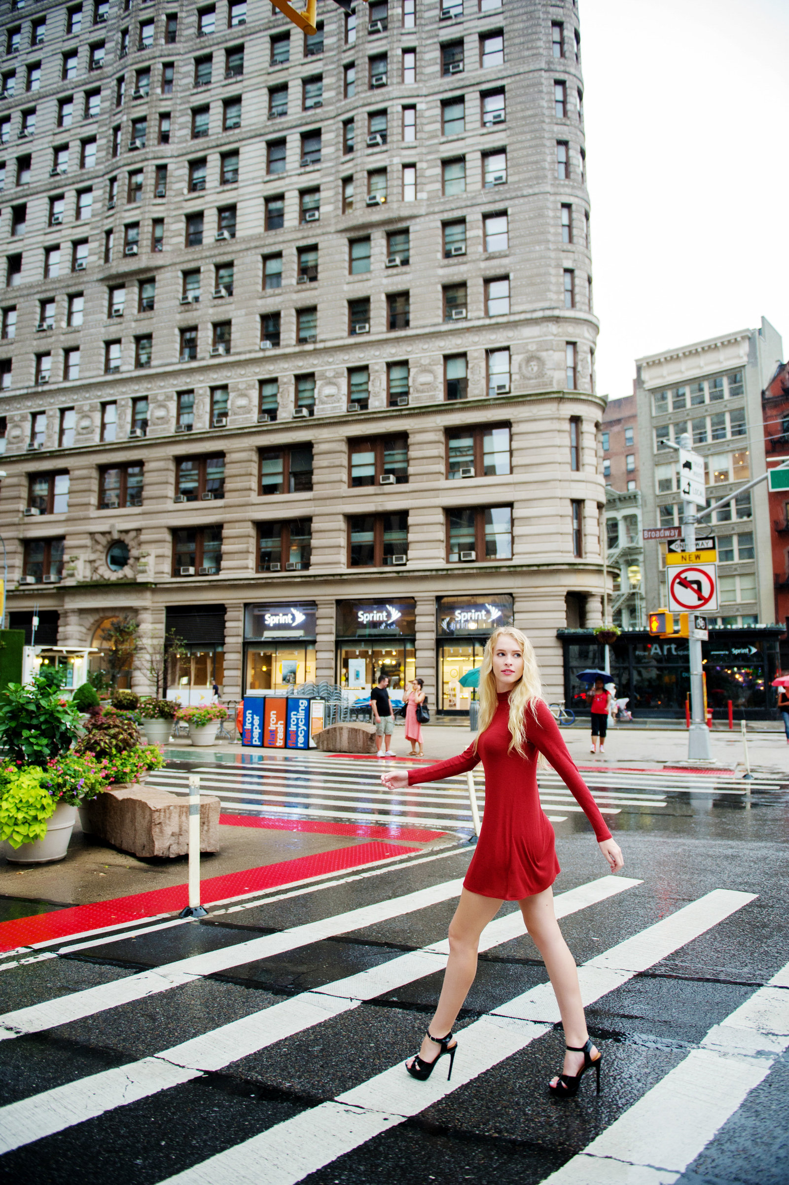 a model in a red dress walks across the street in front of the flat iron building  in nyc