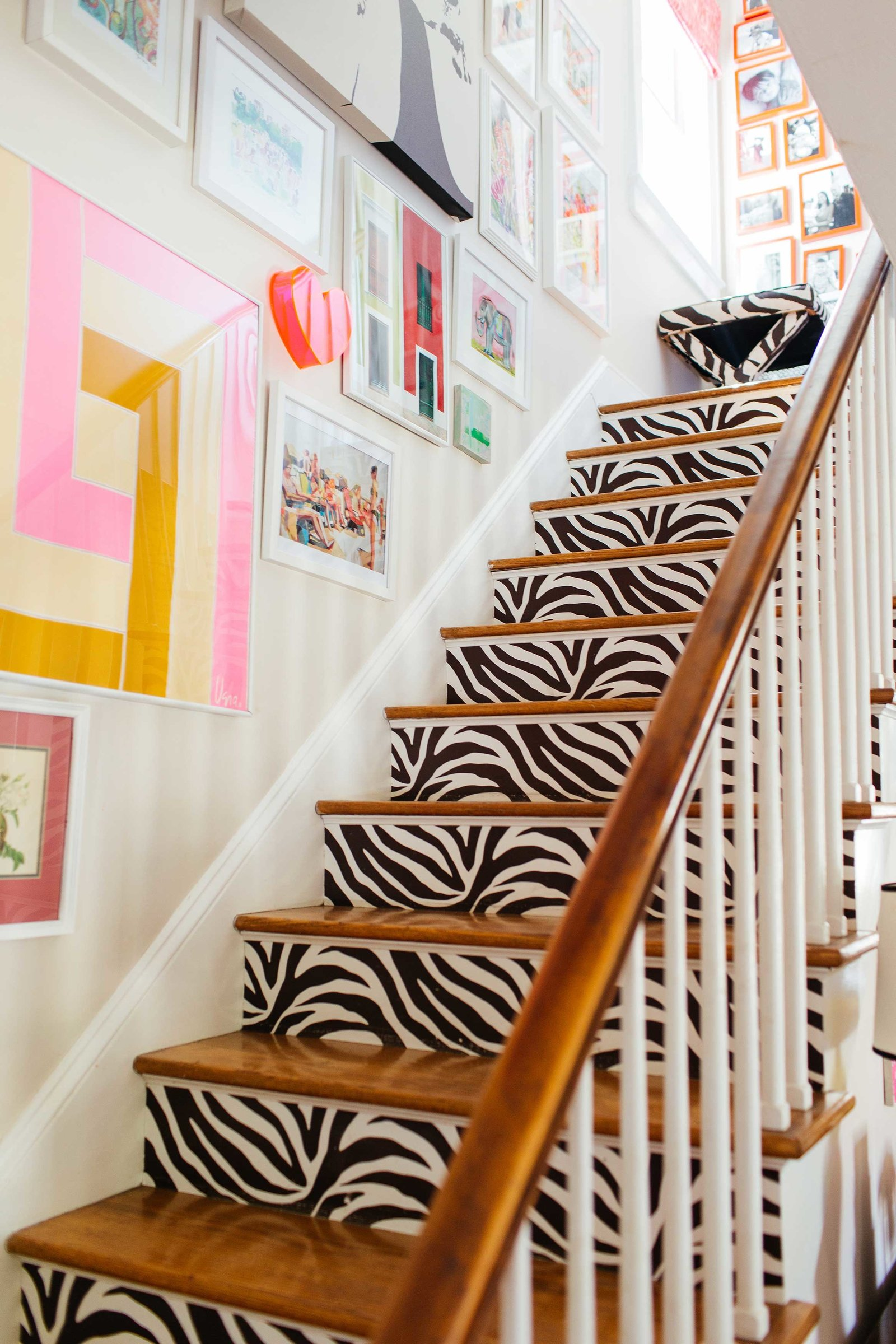 A zebra staircase with a gallery wall of art and photos.