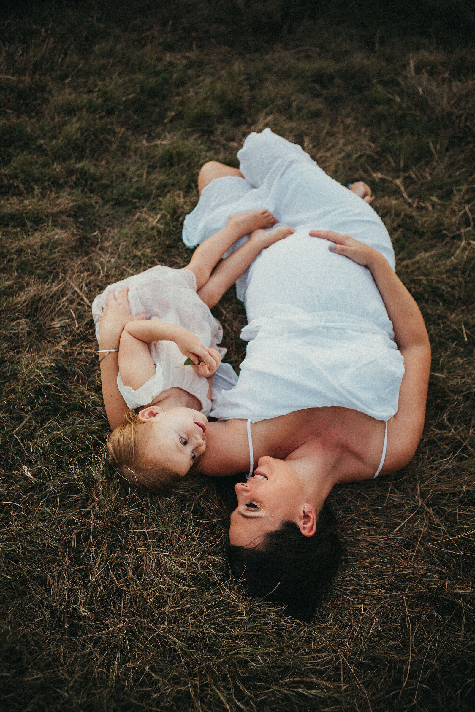 Professional maternity portrait outdoors, mother and daughter lying on grass