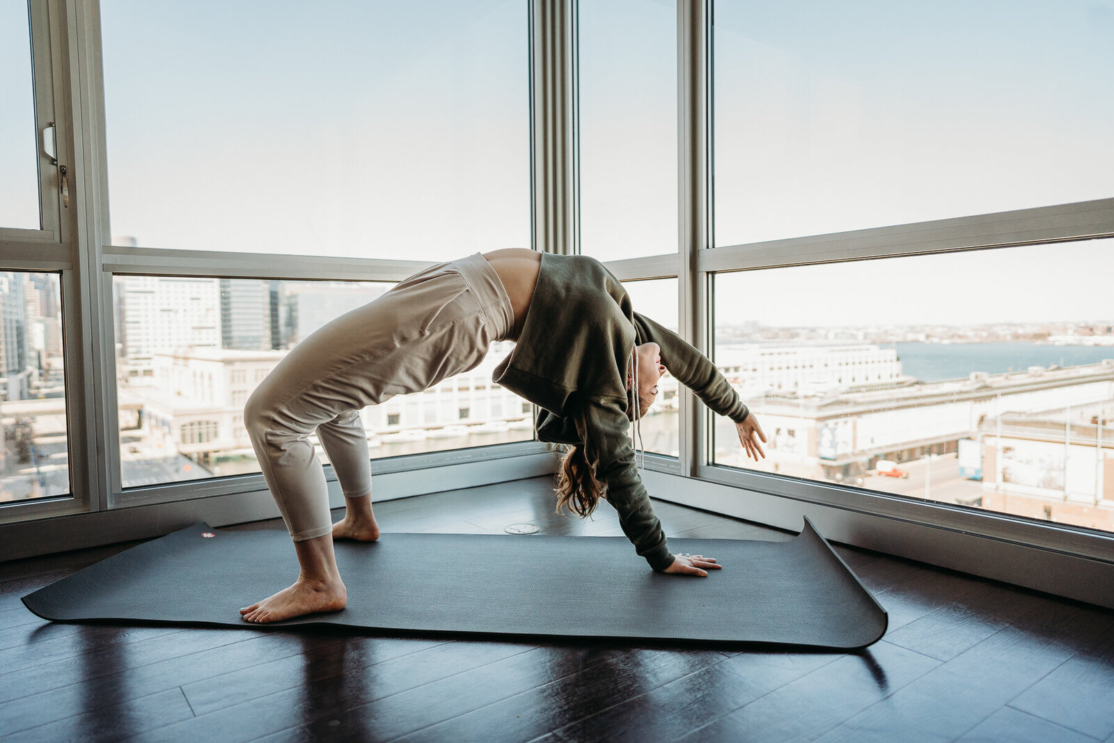 yogi does a back bend in a high rise apartment in boston massachusetts