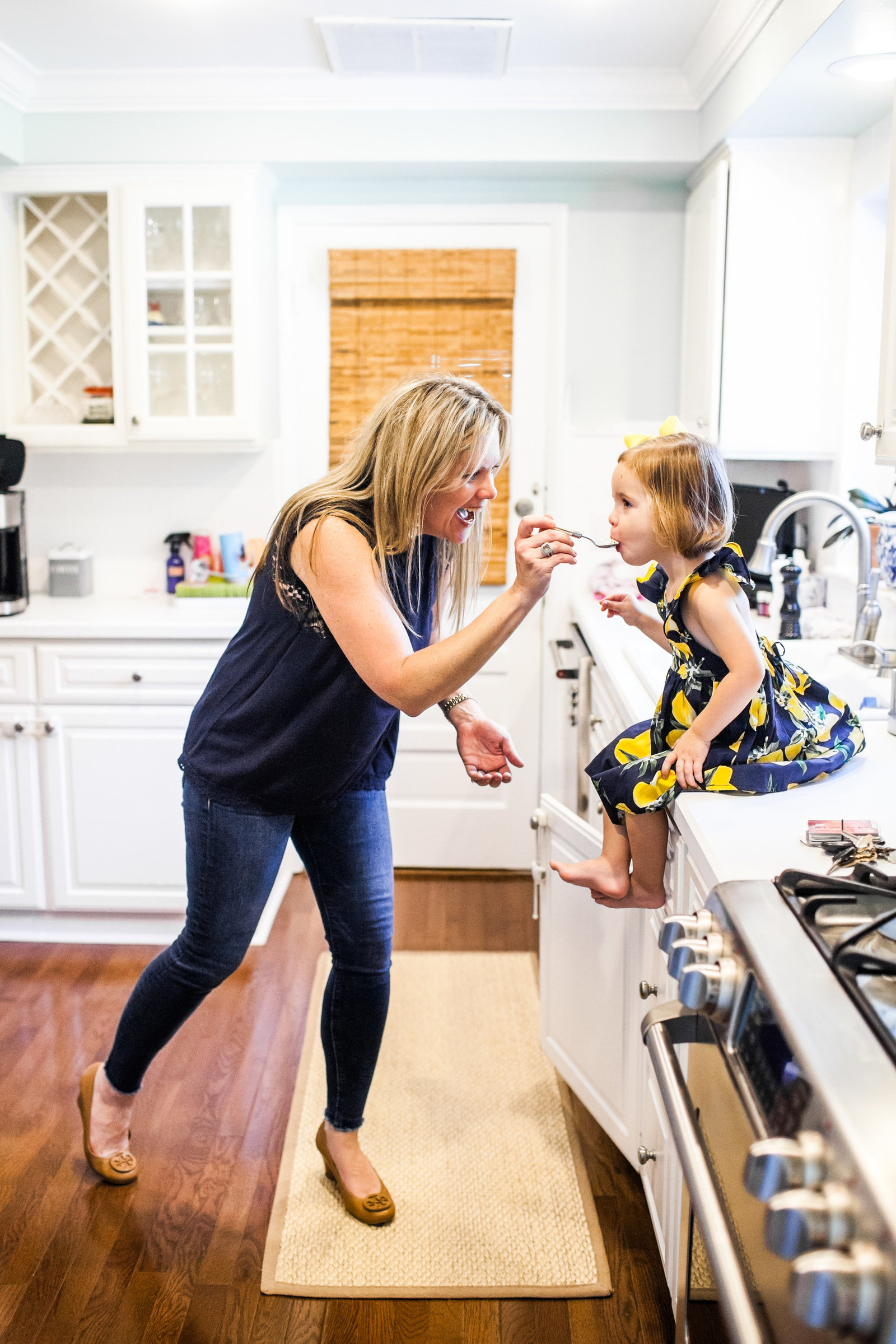 Mom feeding her daughter ice cream in the kitchen