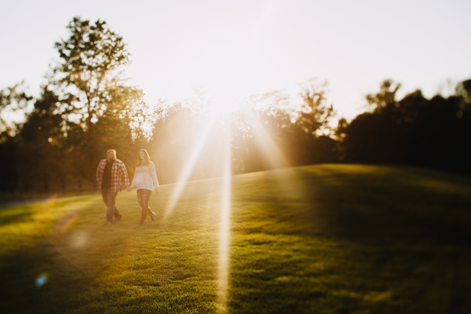 engagement photo of a couple walking through a golf course at sunset
