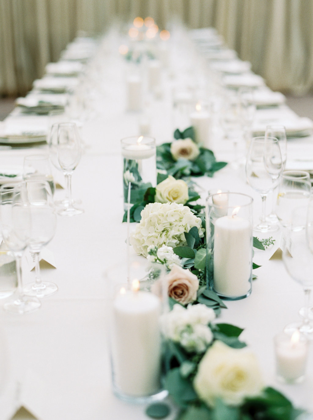 Wedding reception table setting with long eucalyptus garland and white flowers at Butterfly Lane Estate