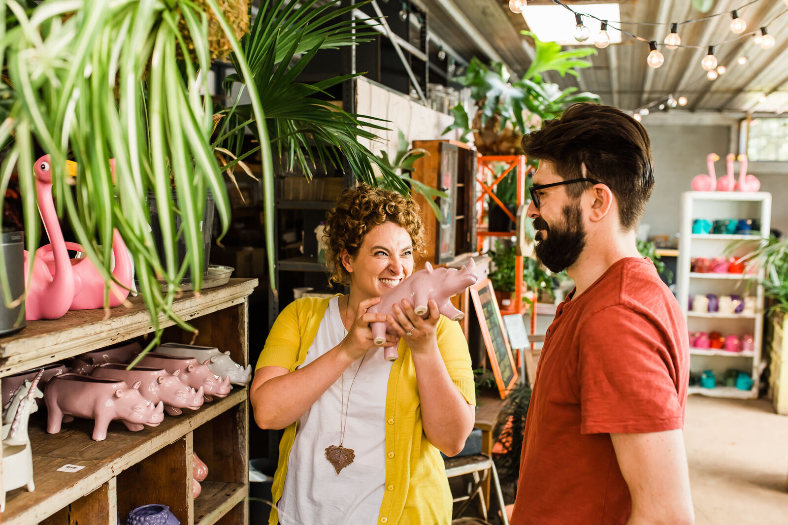 Funny candid photo of an engaged couple shopping for plants together at Flowers and Weeds in St. Louis