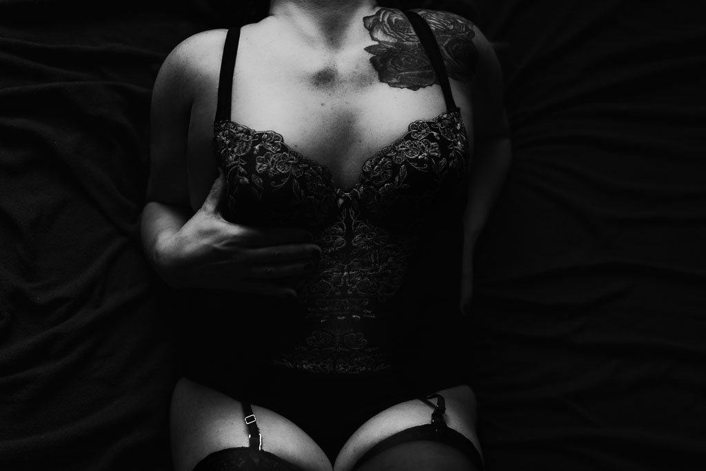 Woman with rose tattoo in black lingerie