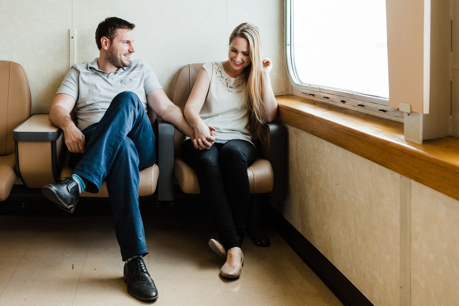 a couple holds hands and laughs together while riding a ferry during their Seattle engagement session with seattle elopement photographer amy galbraith