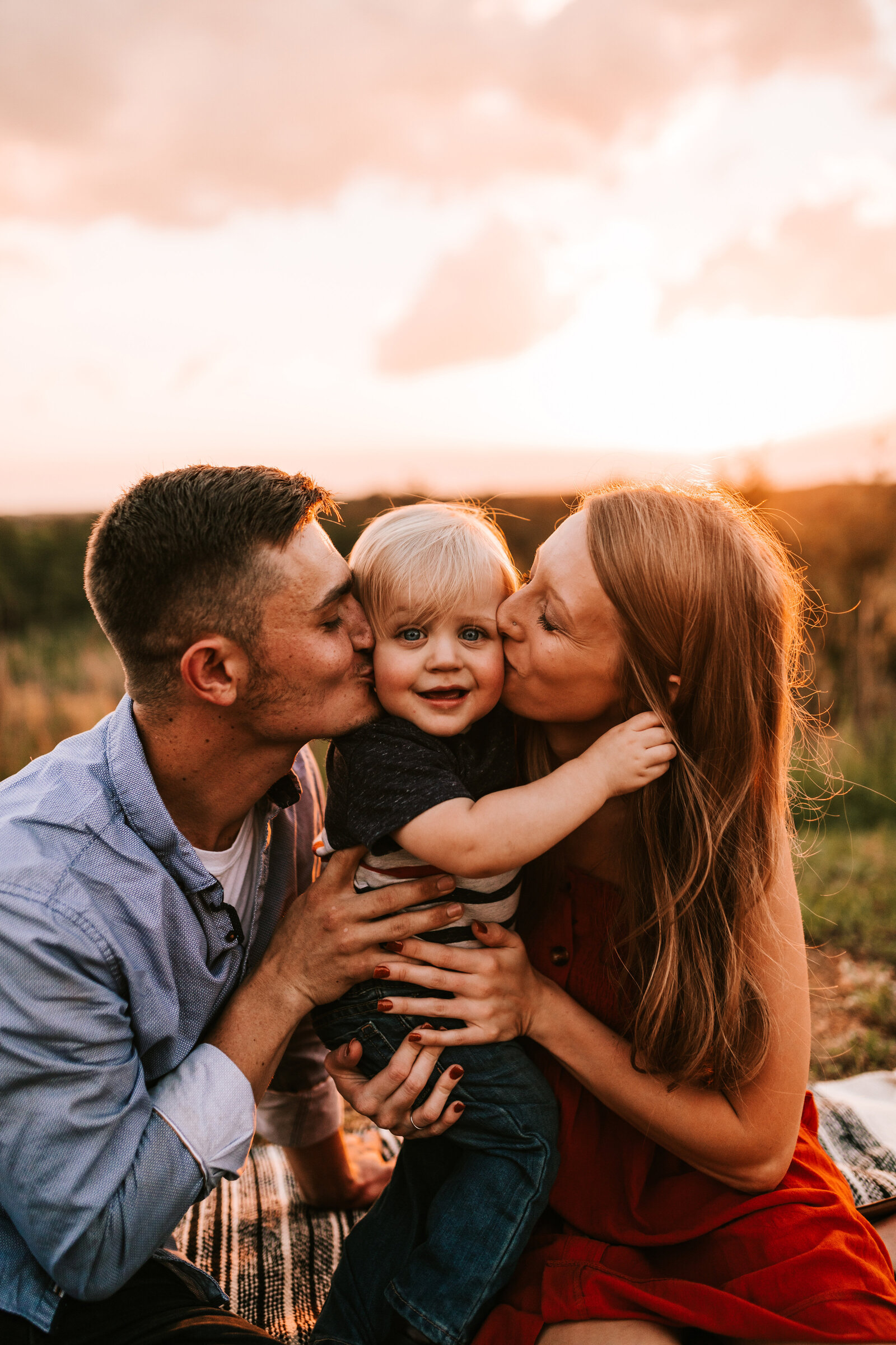 family shoot with mom and dad kissing child with the sunset