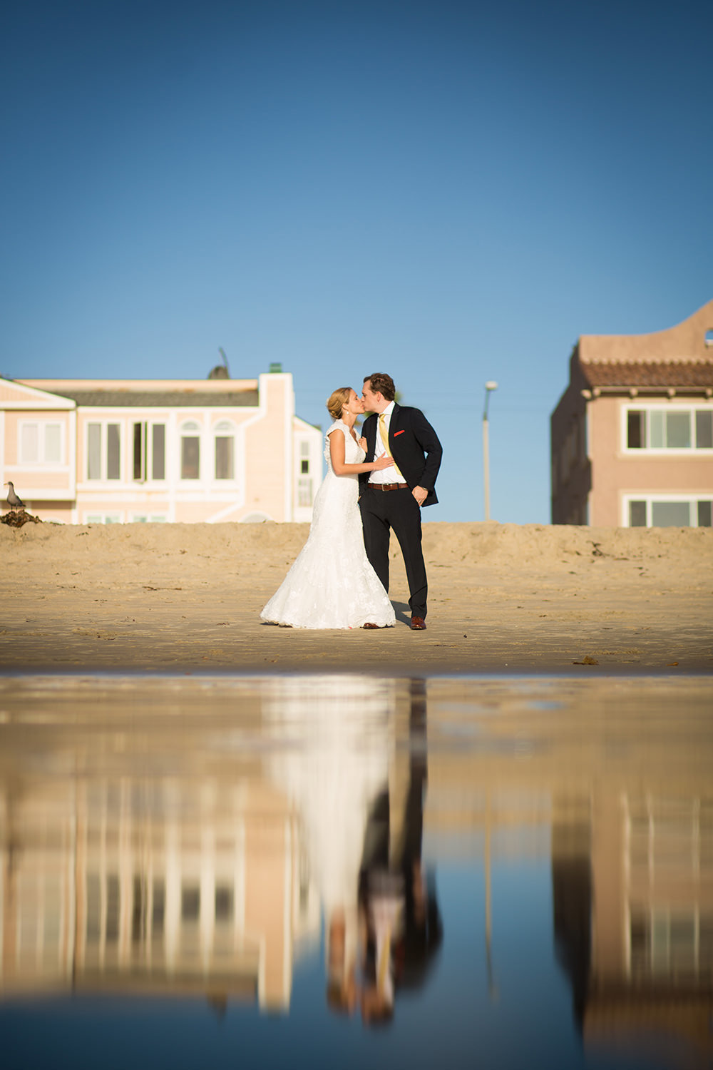 bride and groom by the bay reflecting off the water