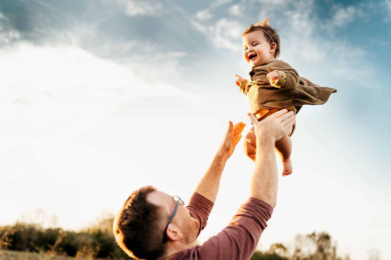dad tossing baby into the air