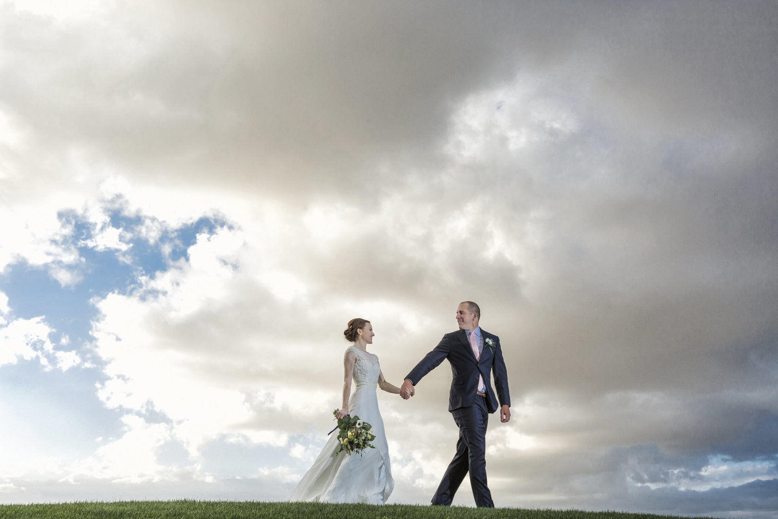 wedding couple holding hand on a hill with epic clouds