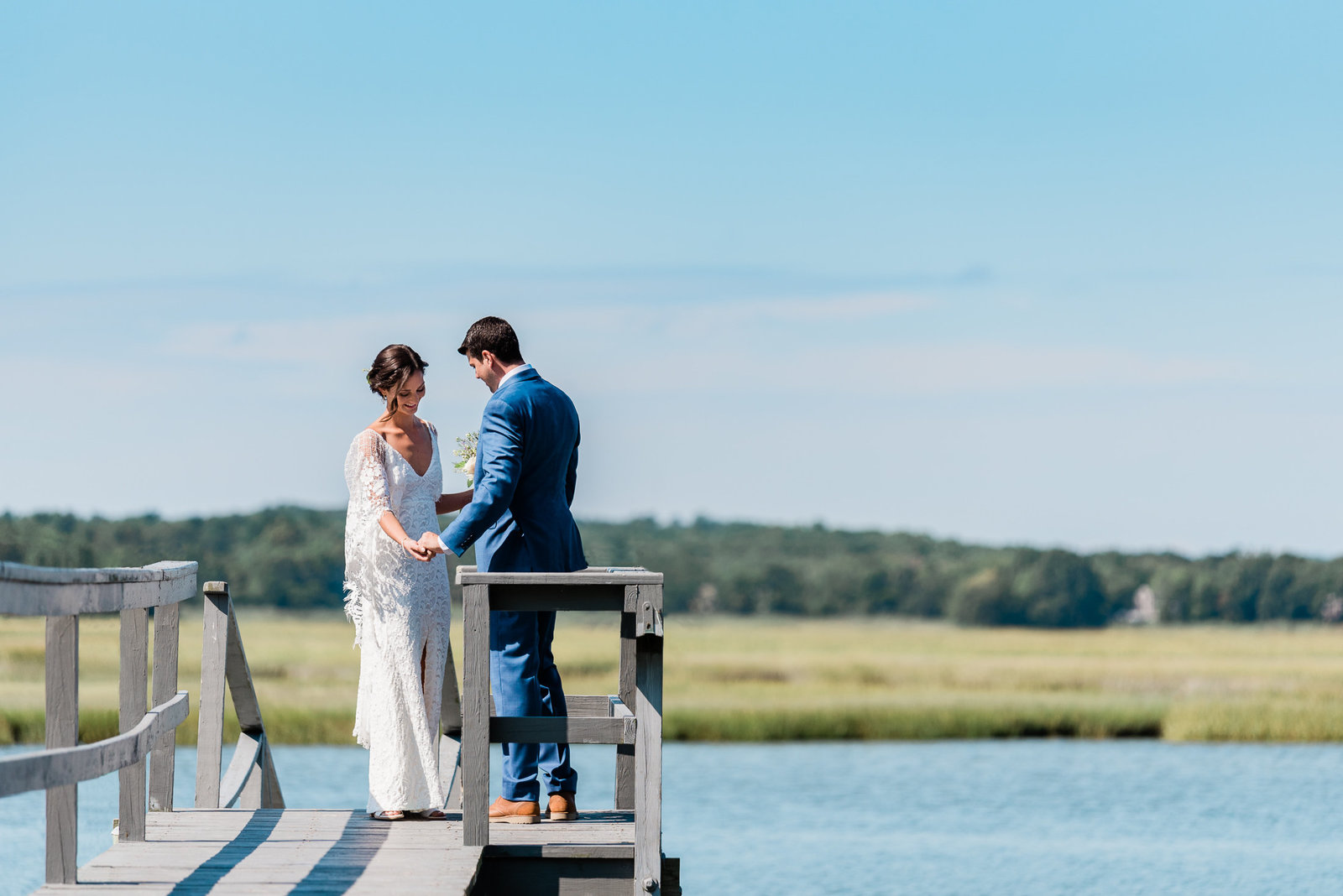 A bride and groom have their first look at the end of a dock overlooking back river before their duxbury, MA wedding at a private home on powder point