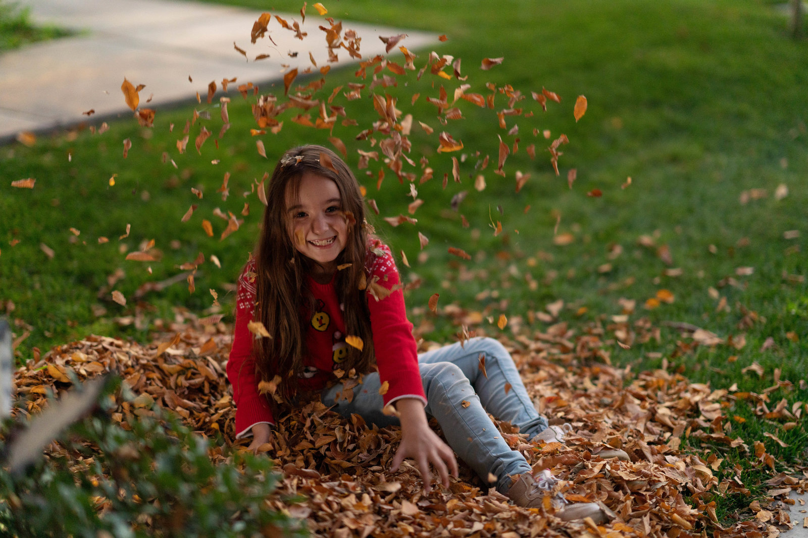 Lifestyle portrait of girl playing in leaves