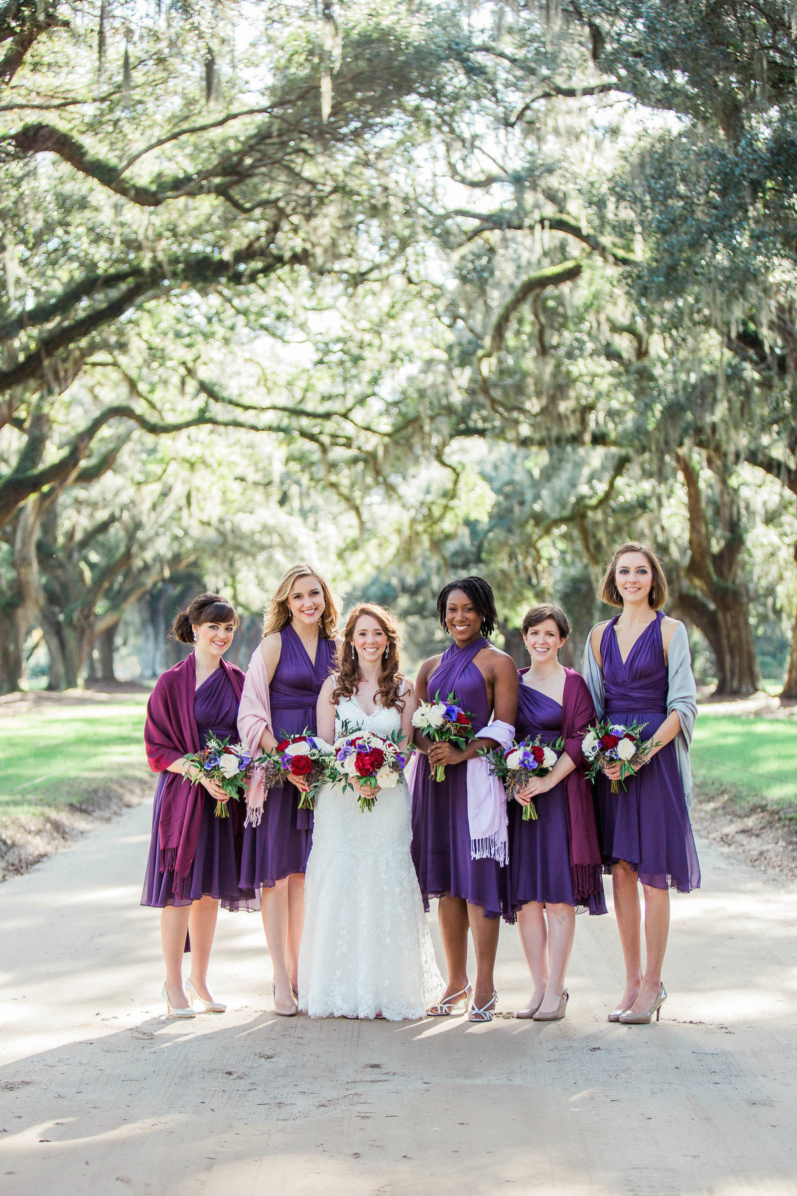 Bride and bridesmaids stand on avenue of oaks, Boone Hall Plantation, Charleston, South Carolina