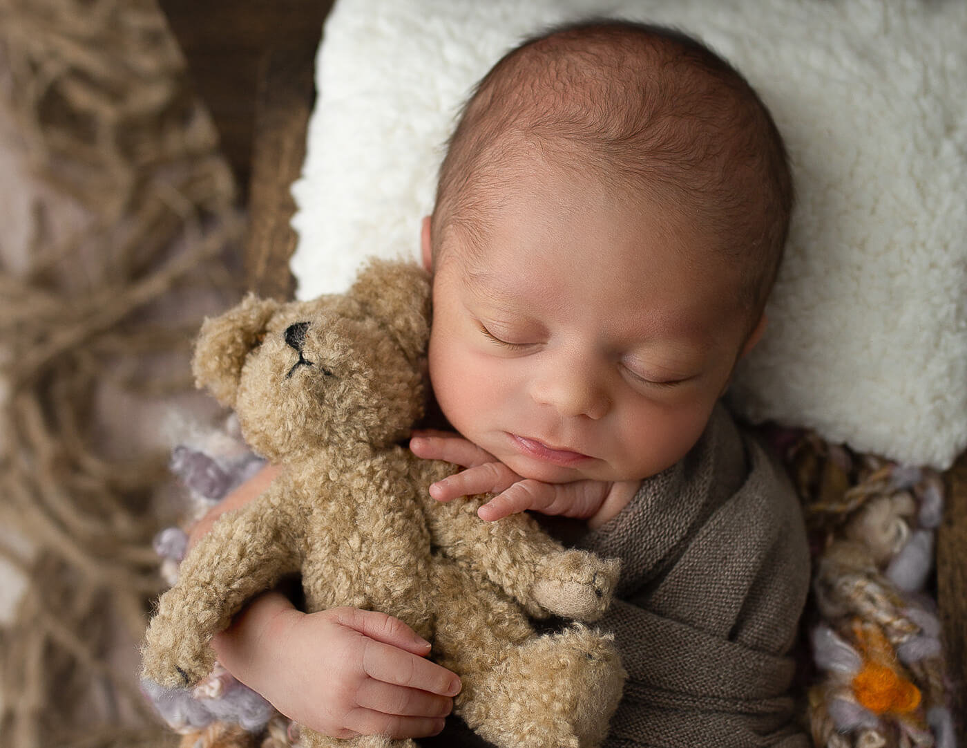Precious newborn holding a teddy bear in our Rochester, NY studio.