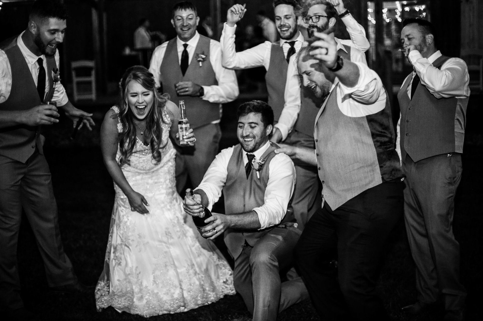 Bridal party laughs as groomsman aatempts to open a bottle of champagne