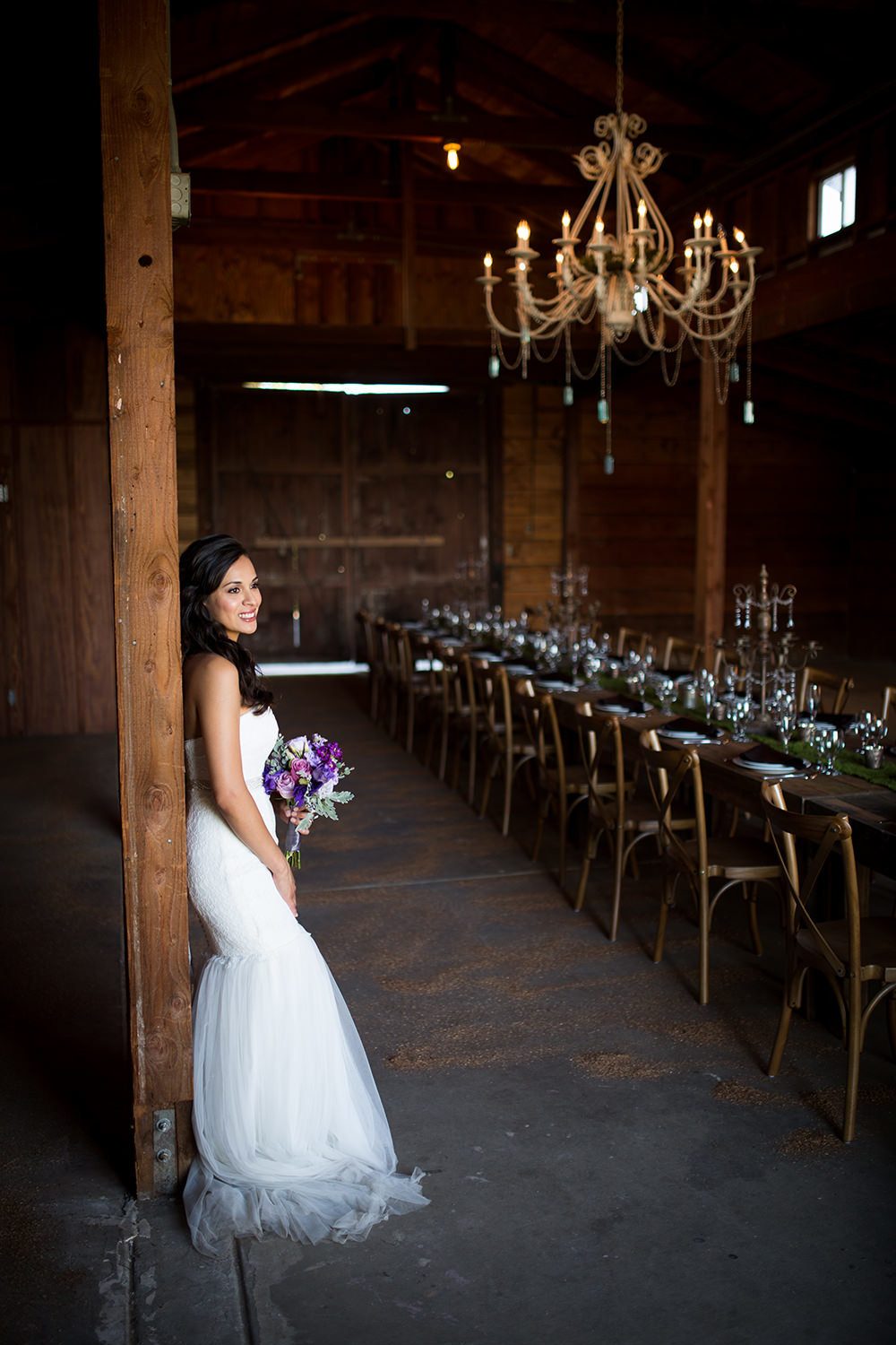 bride in rustic barn with farm tables