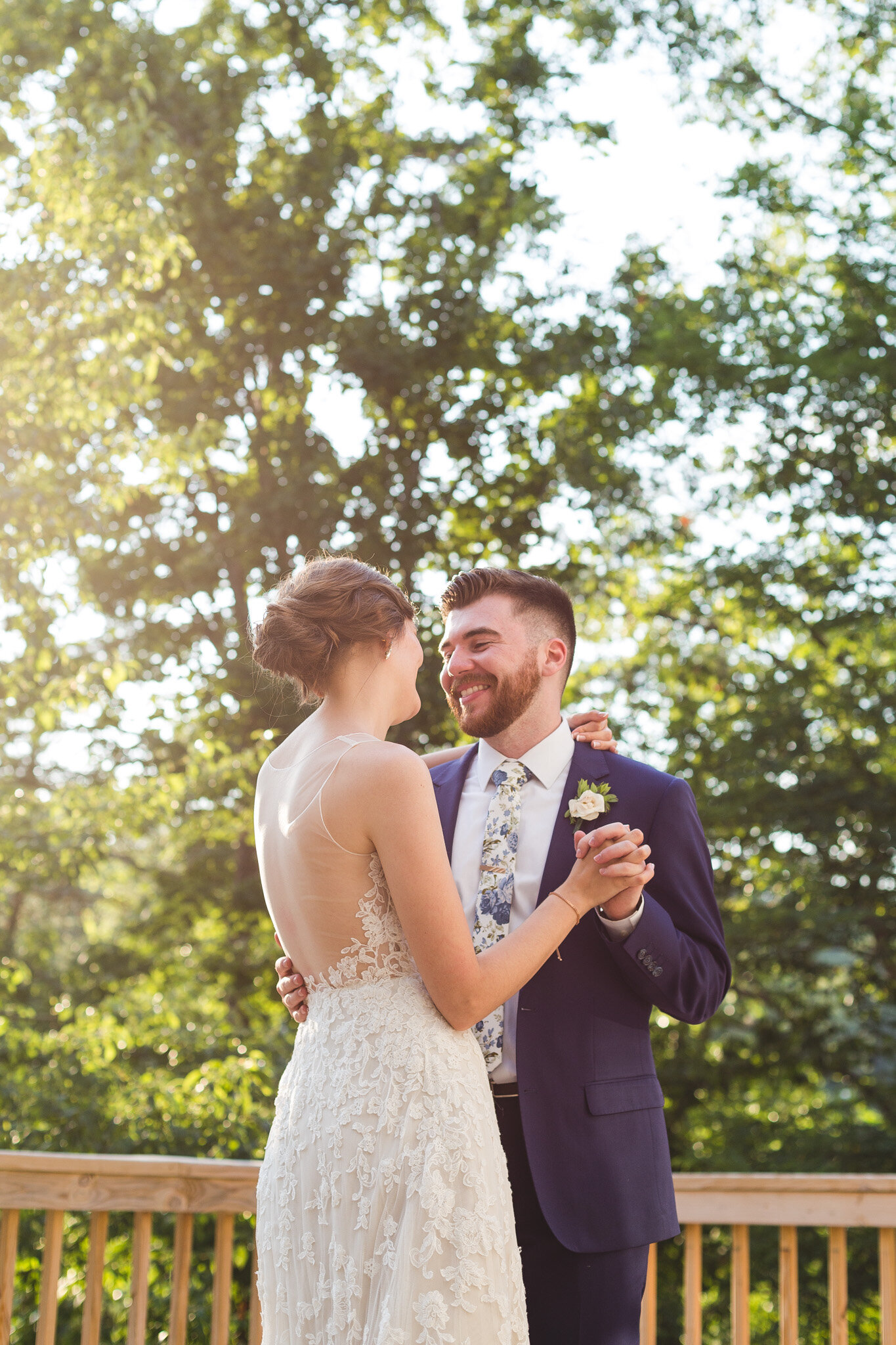 bride and groom first dance on deck during golden hour for micro wedding