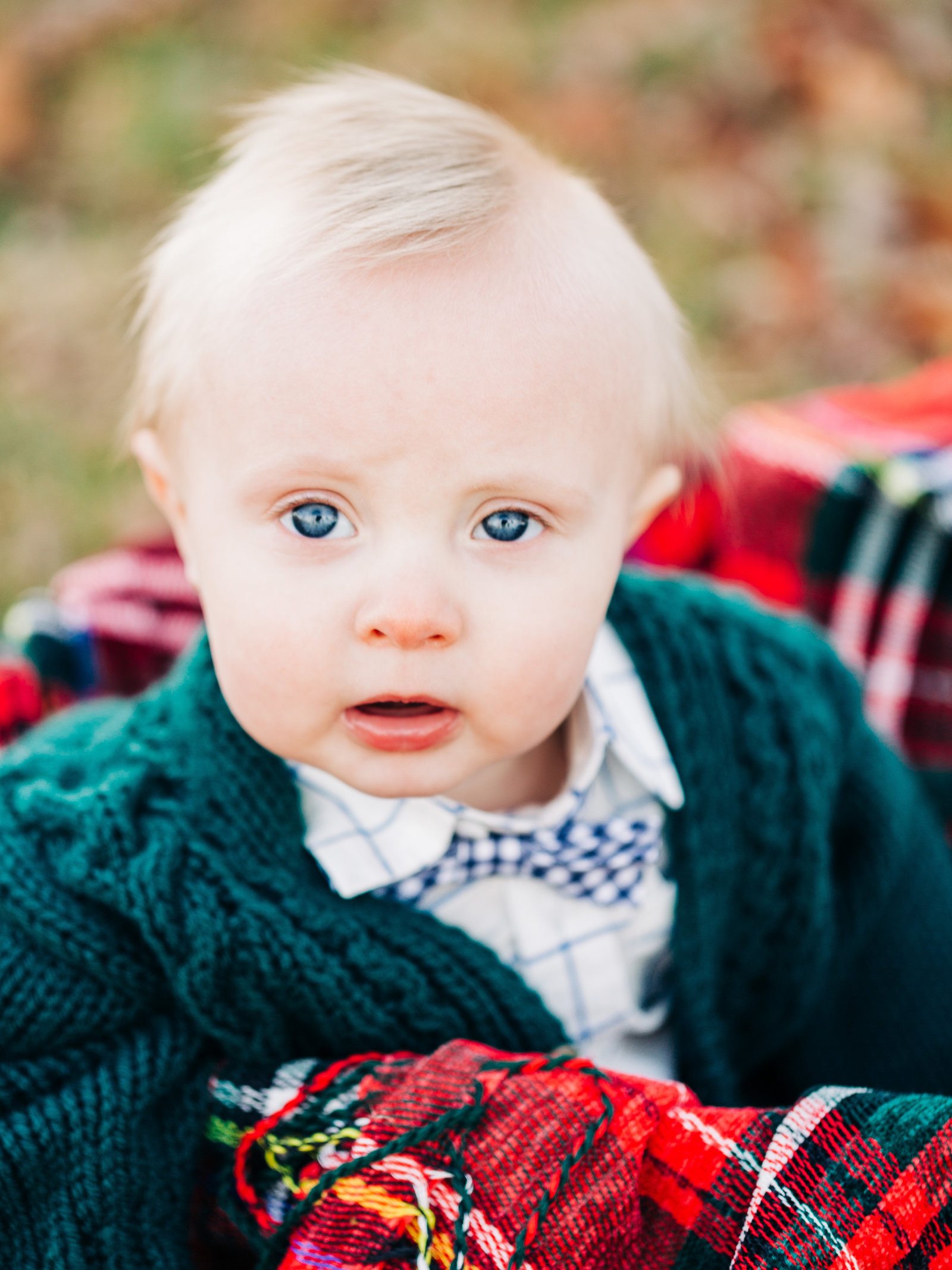 Baby in green sweater sits in a silver tub with red plaid blanket