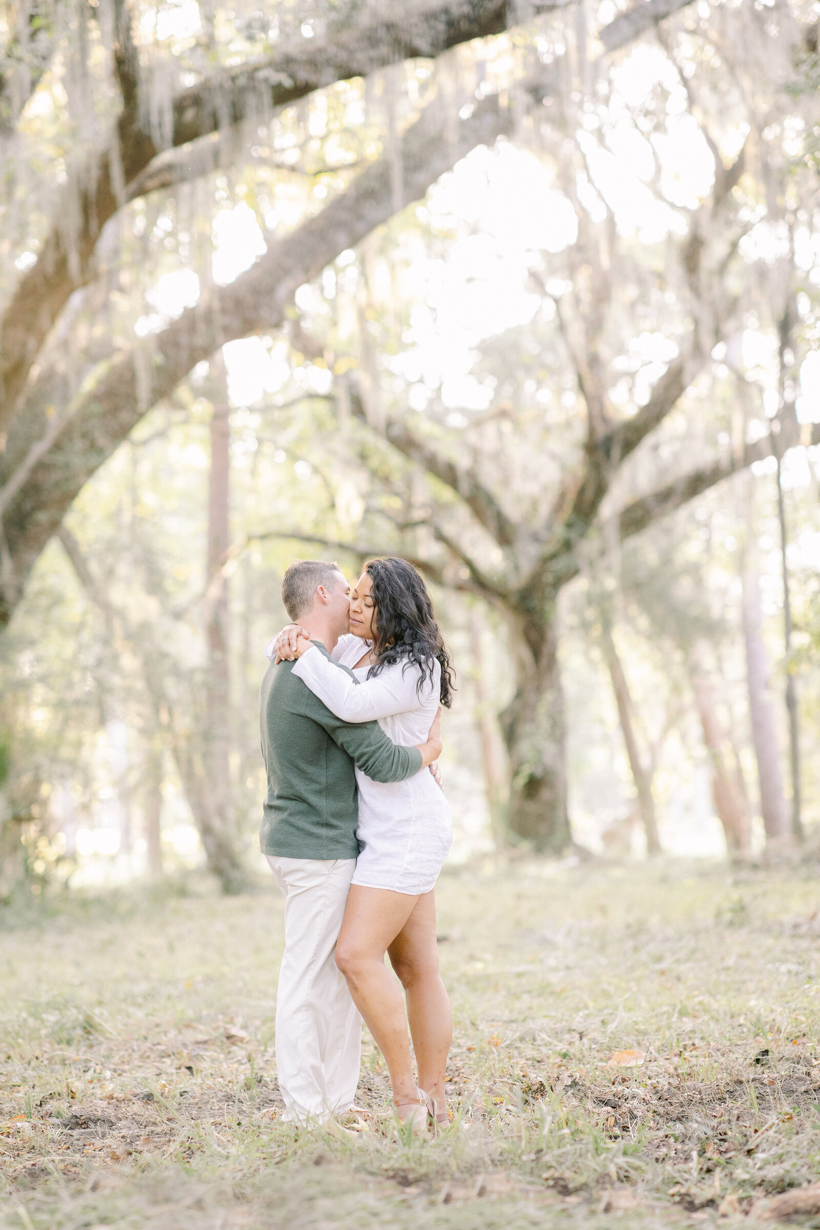 Man and Woman hug surrounded by large live oak tress and spanish moss.