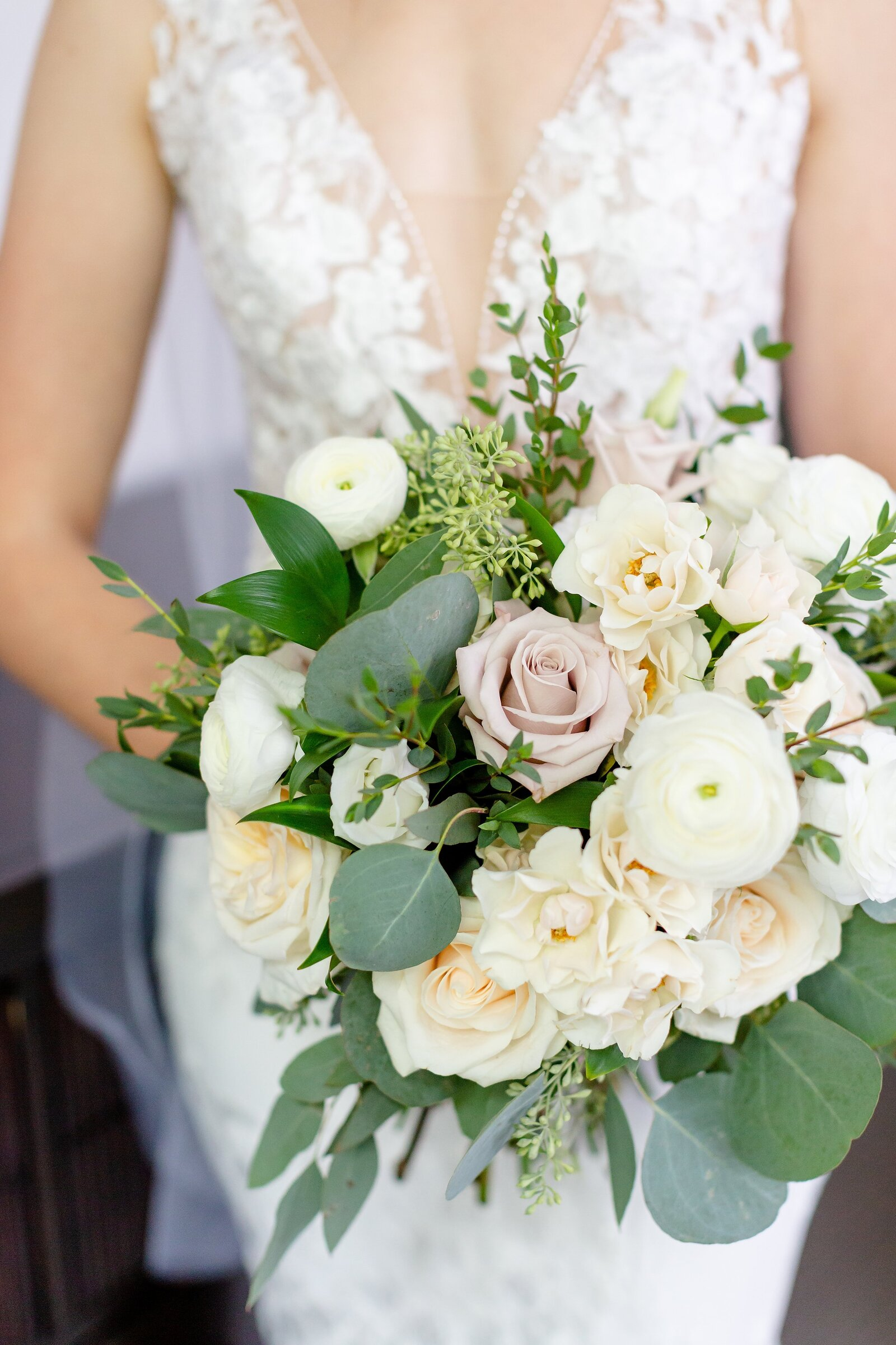 Bride-holds-her-beautiful-wedding-bouquet-by-Springhill-flowers-at-windermere-manor