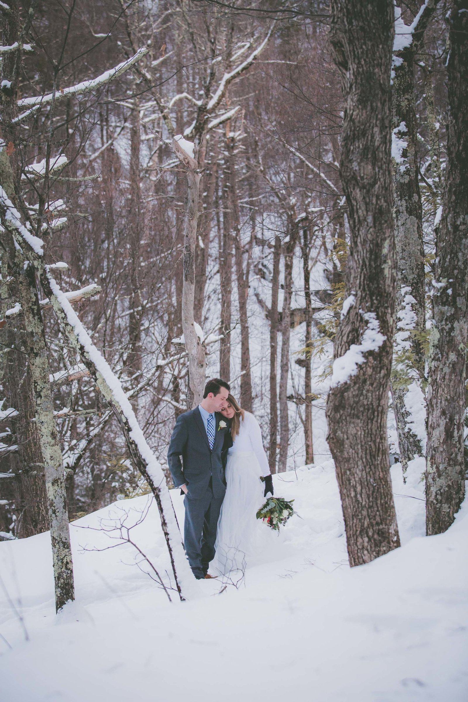 Bride and groom close eyes and cuddle each other among upstate New York snow covered trees.
