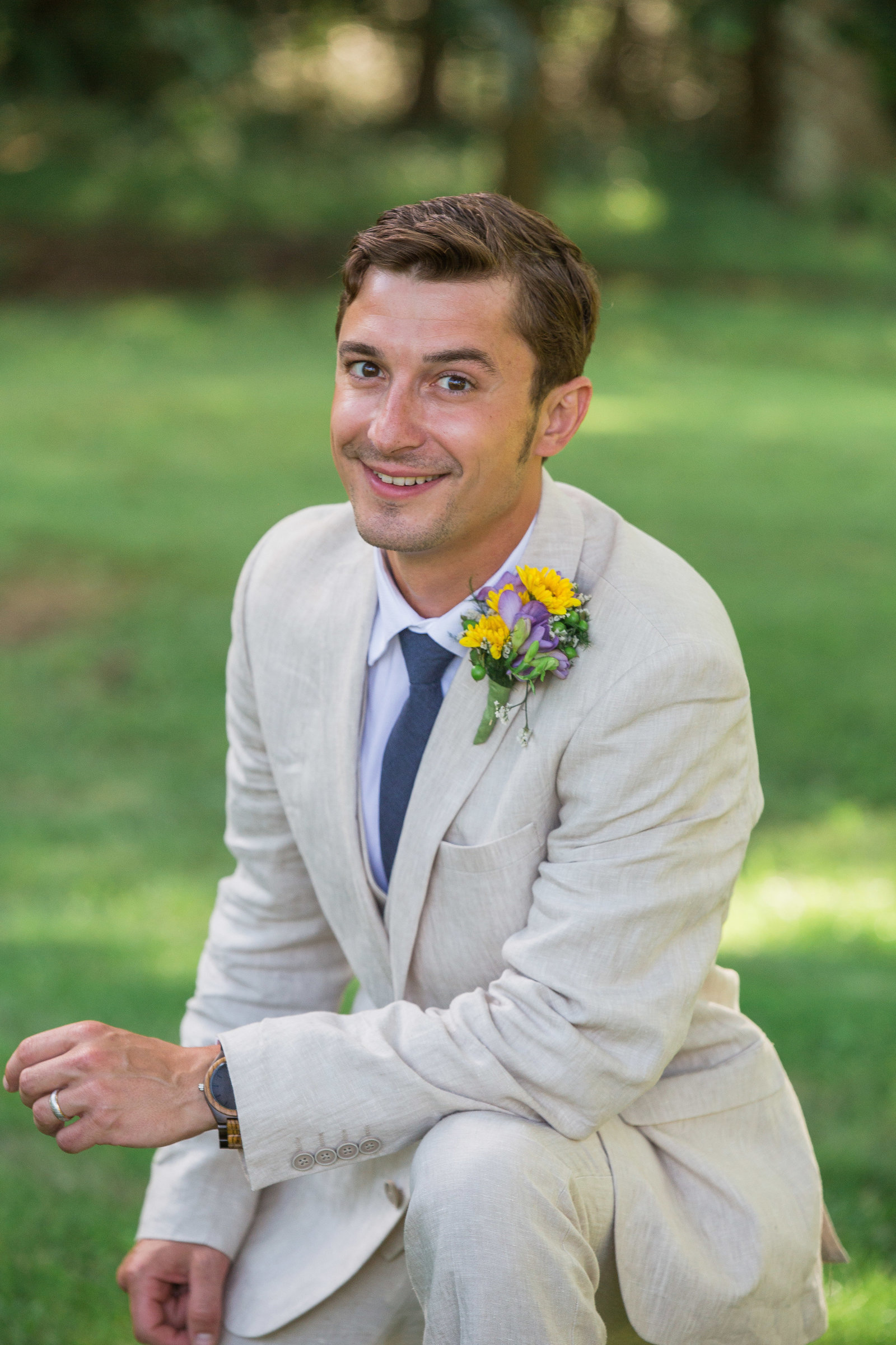 groom in a tan suit kneels on the grass