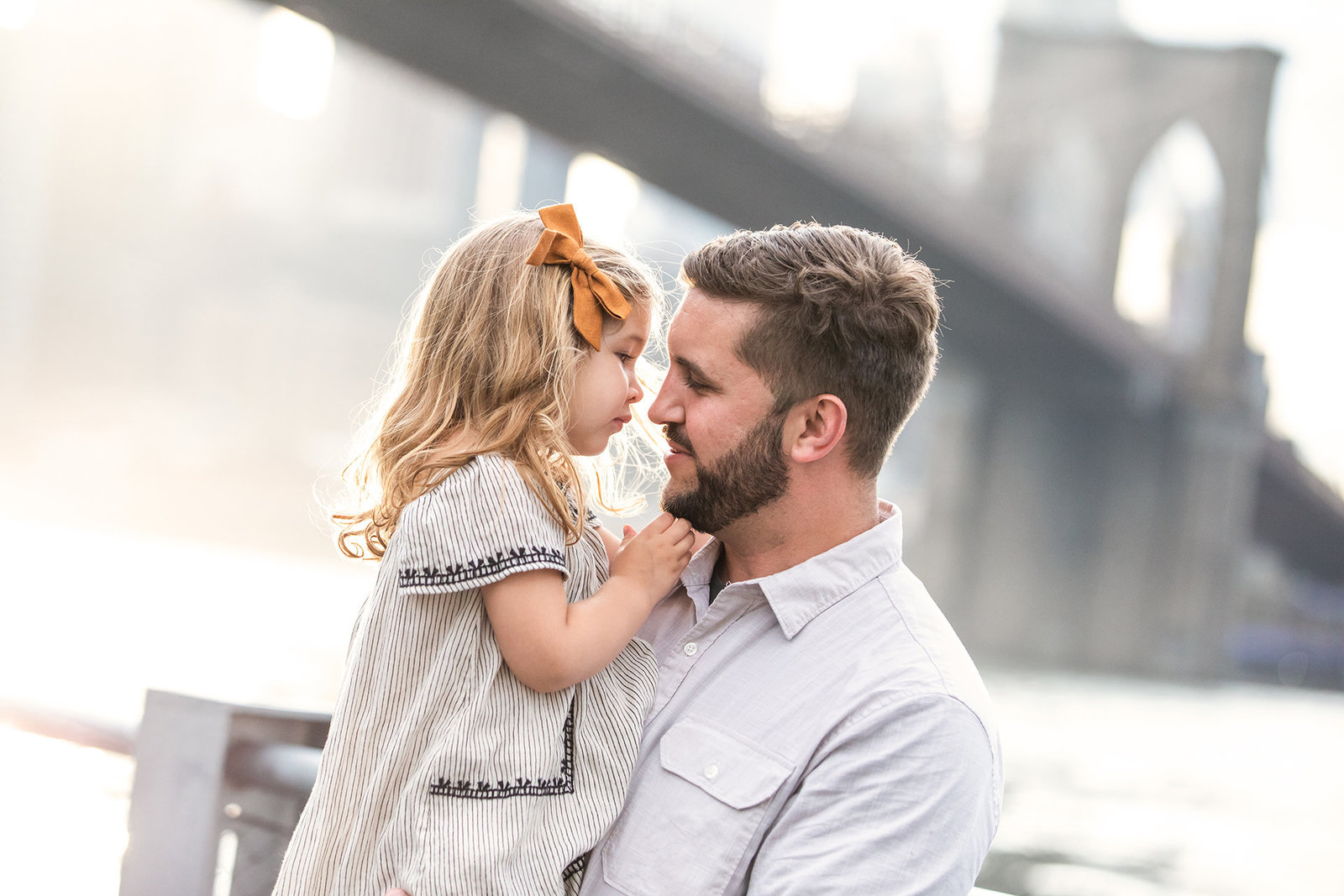 father and daughter in front of the Brooklyn Bridge
