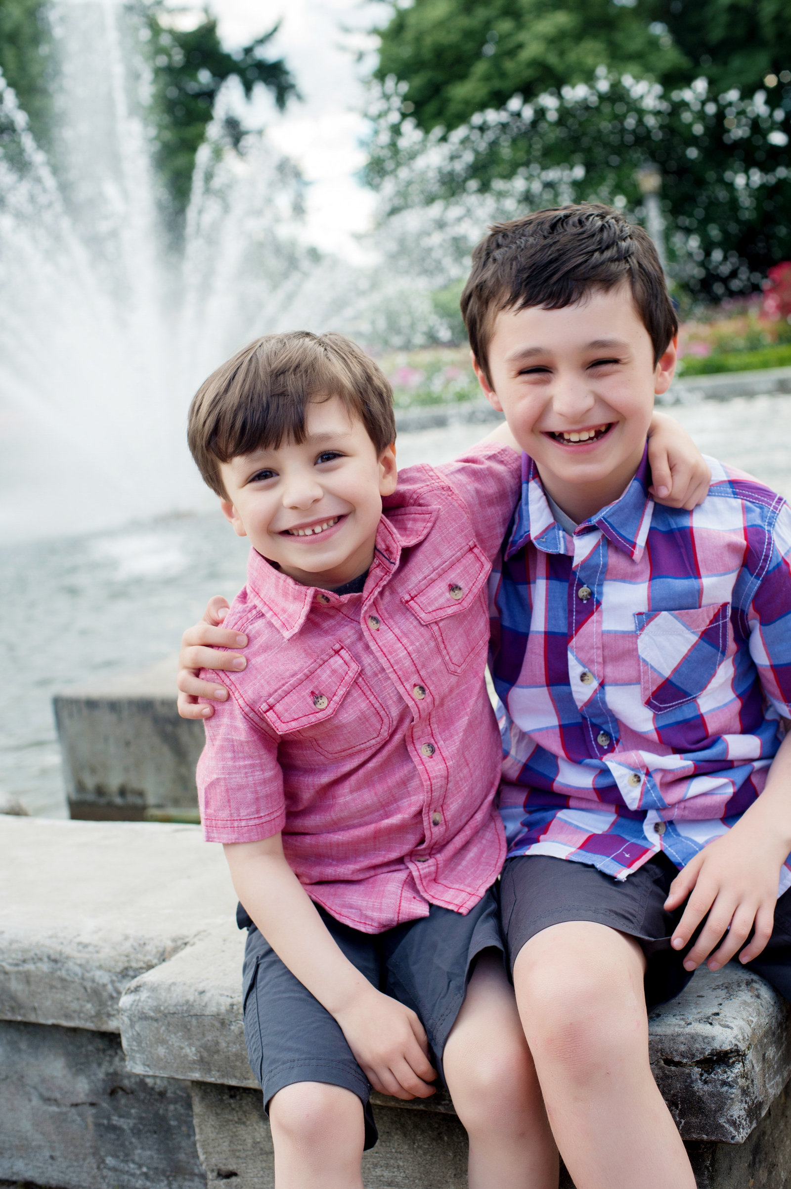 brothers laugh at the camera as they sit on the fountain at peninsula park
