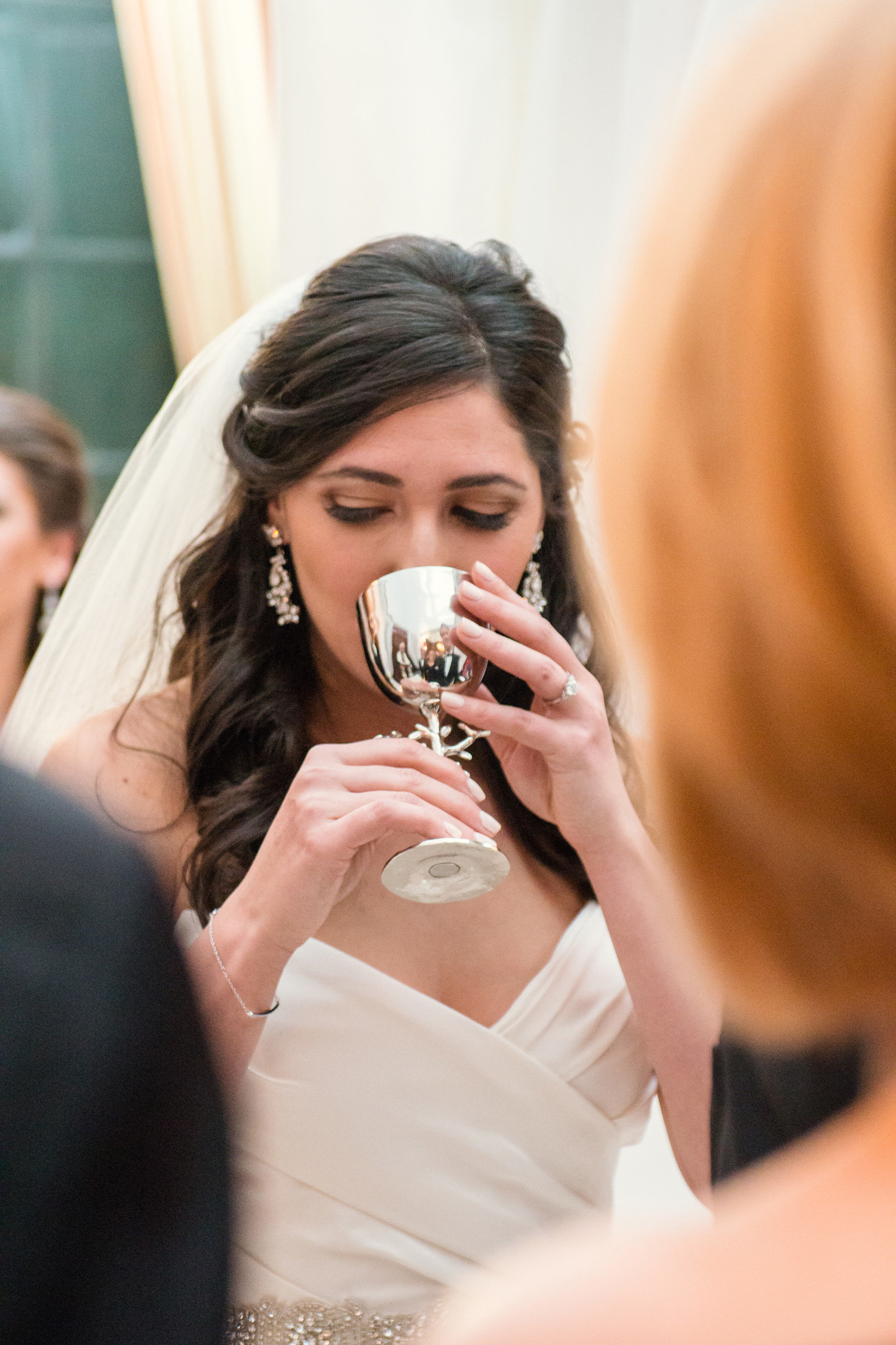 bride drinking out of the wine cup during her wedding ceremony