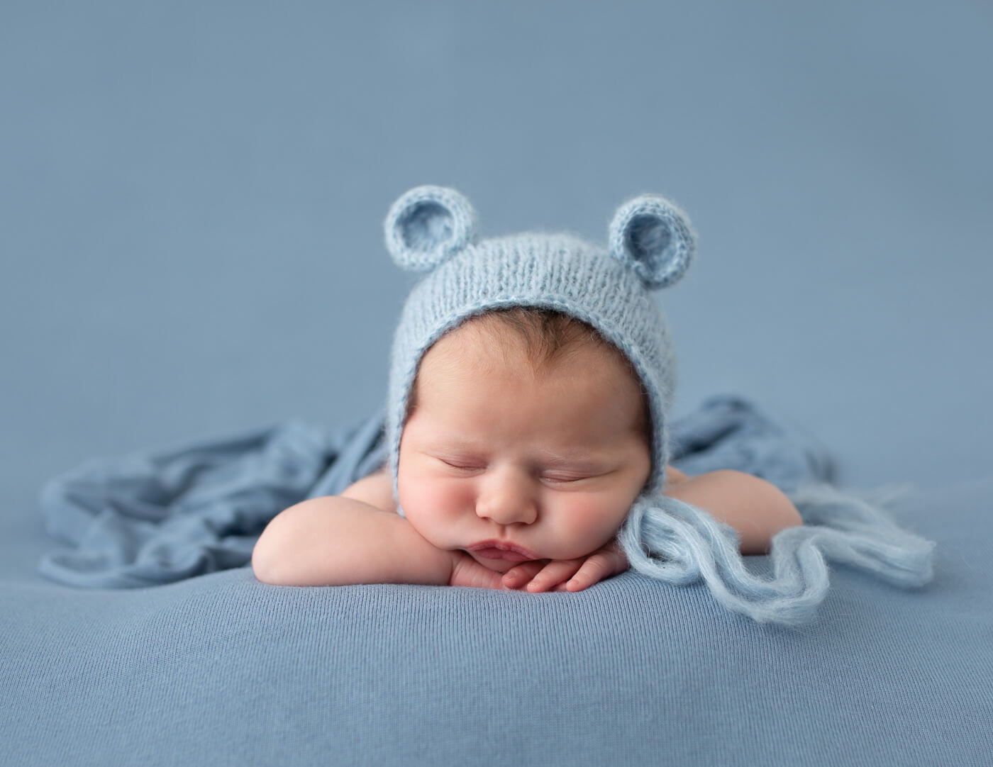 Precious newborn boy in head on hands pose.