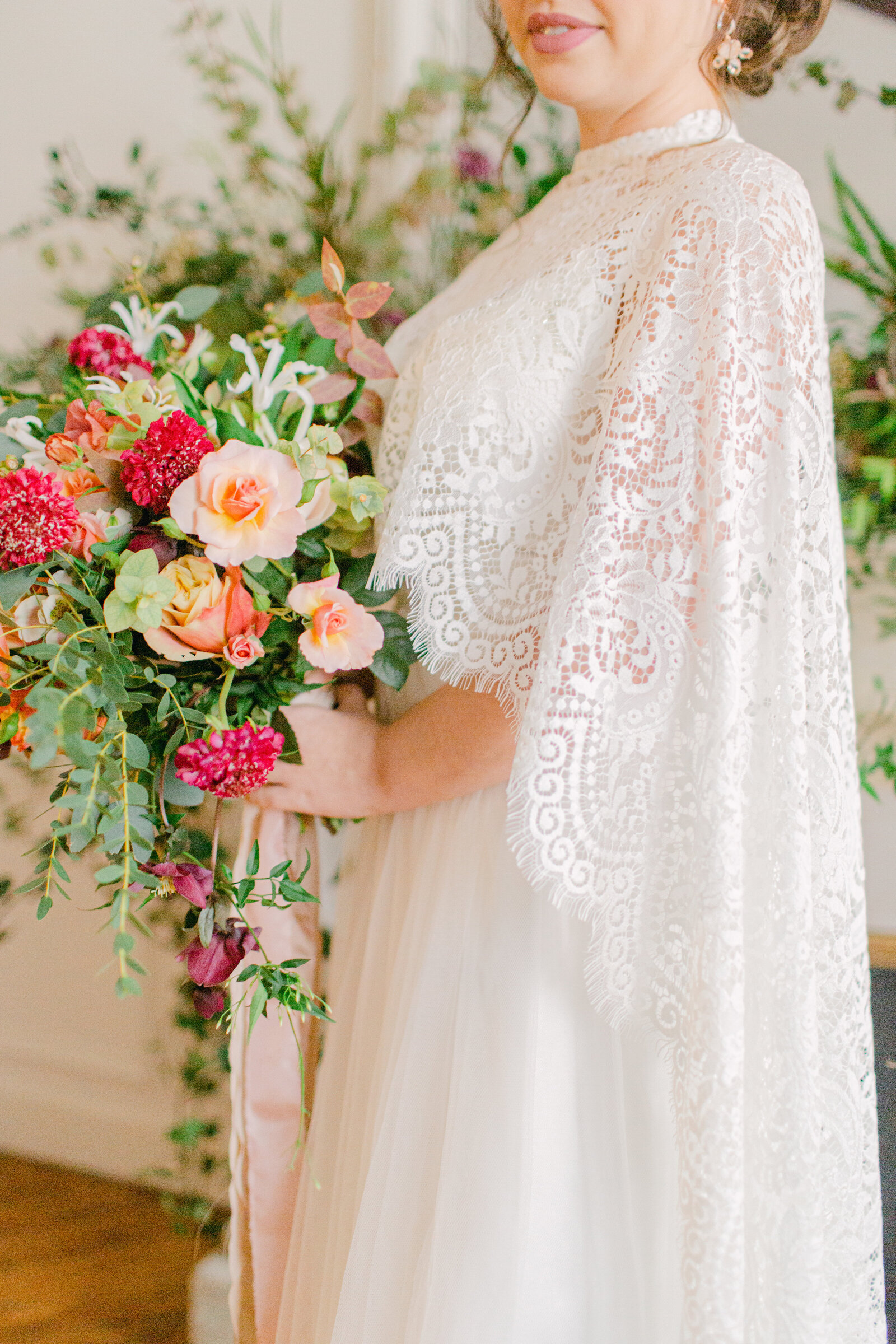 bride holding bouquet of flowers wearing a lace cape and standing in front of a fireplace mantel in paris apartment