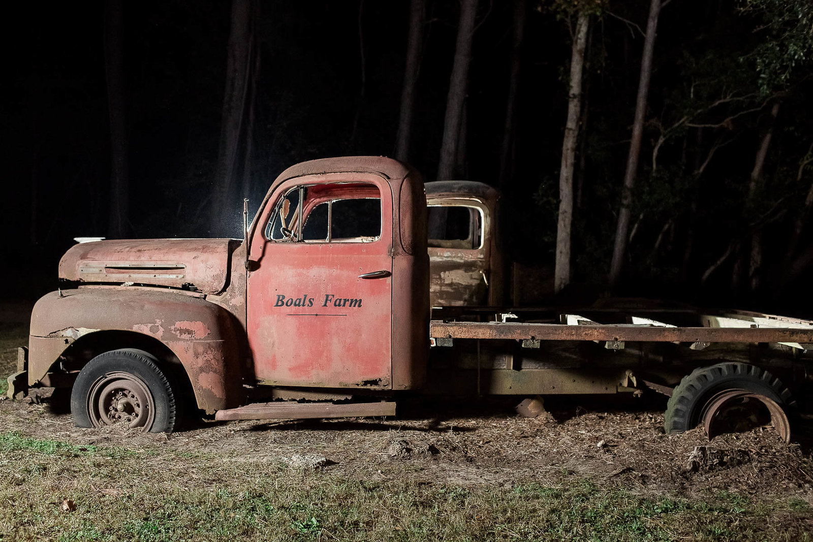 Rustic red truck sits in woods, Boals Farm, Charleston, South Carolina