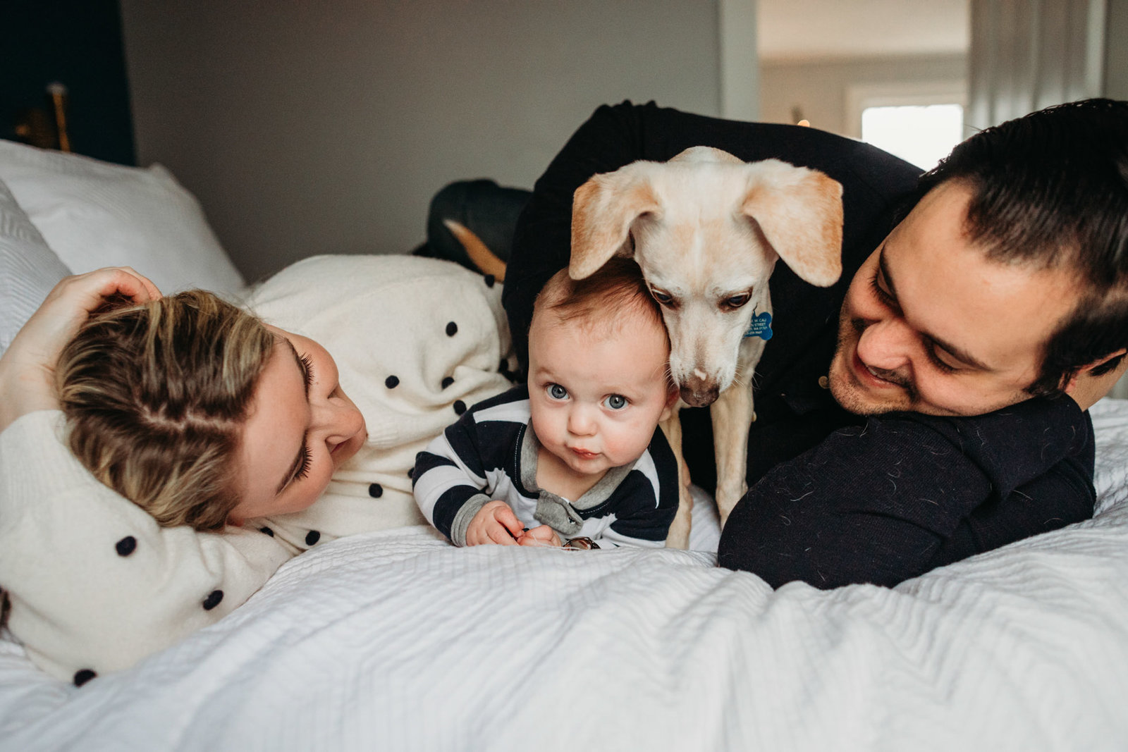 family lies on bed with baby boy and puppy during ashland family photos