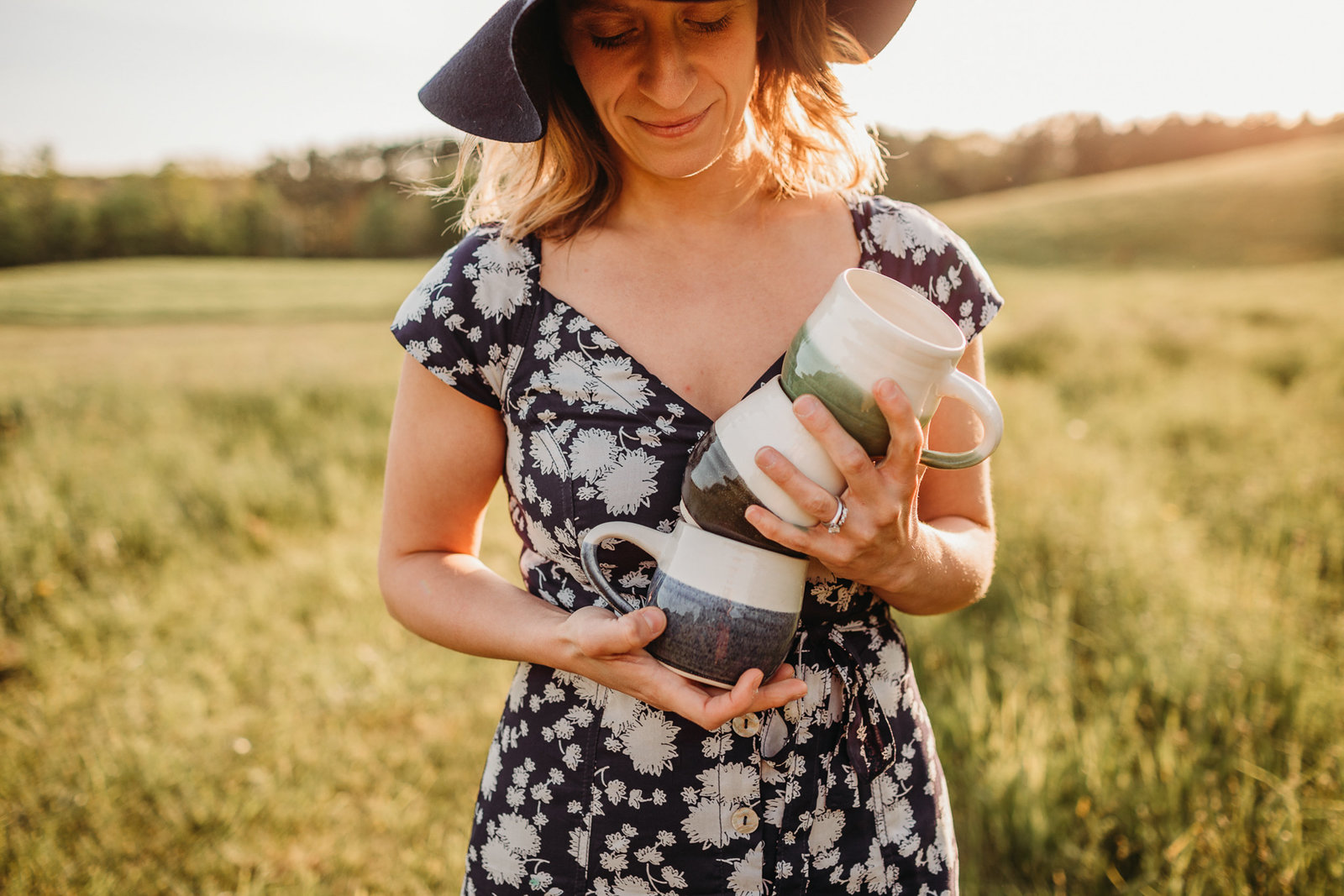 woman holds three hand crafted mugs in a field at sunset