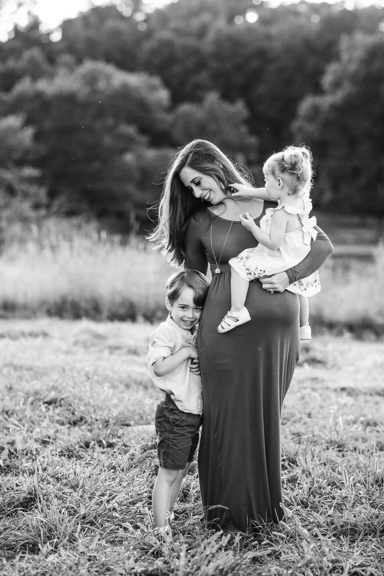 pregnant mother snuggles older siblings during outdoor maternity session in southborough ma