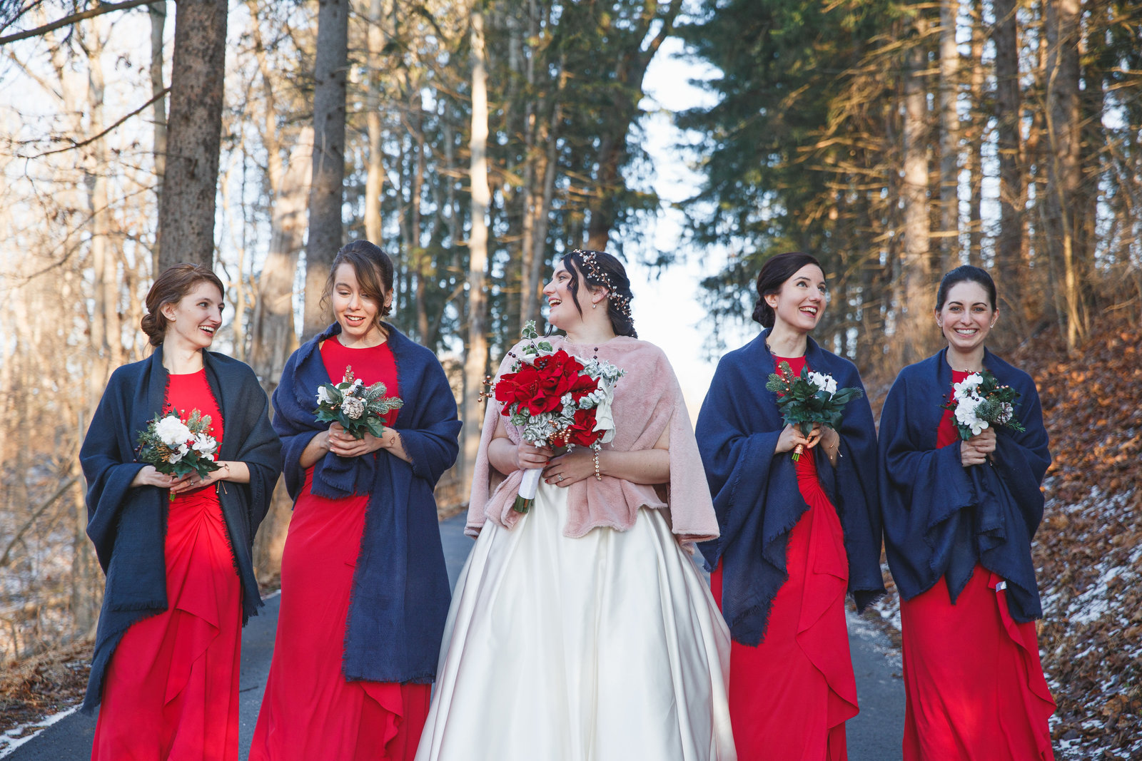 bride laughs with her bridesmaids as they walk through boyce park holding their bouquets