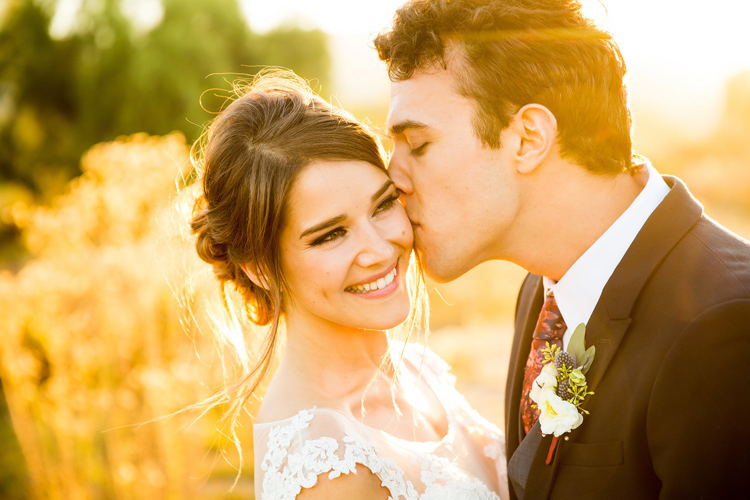 Groom Kissing Bride on the Cheek at Sunset